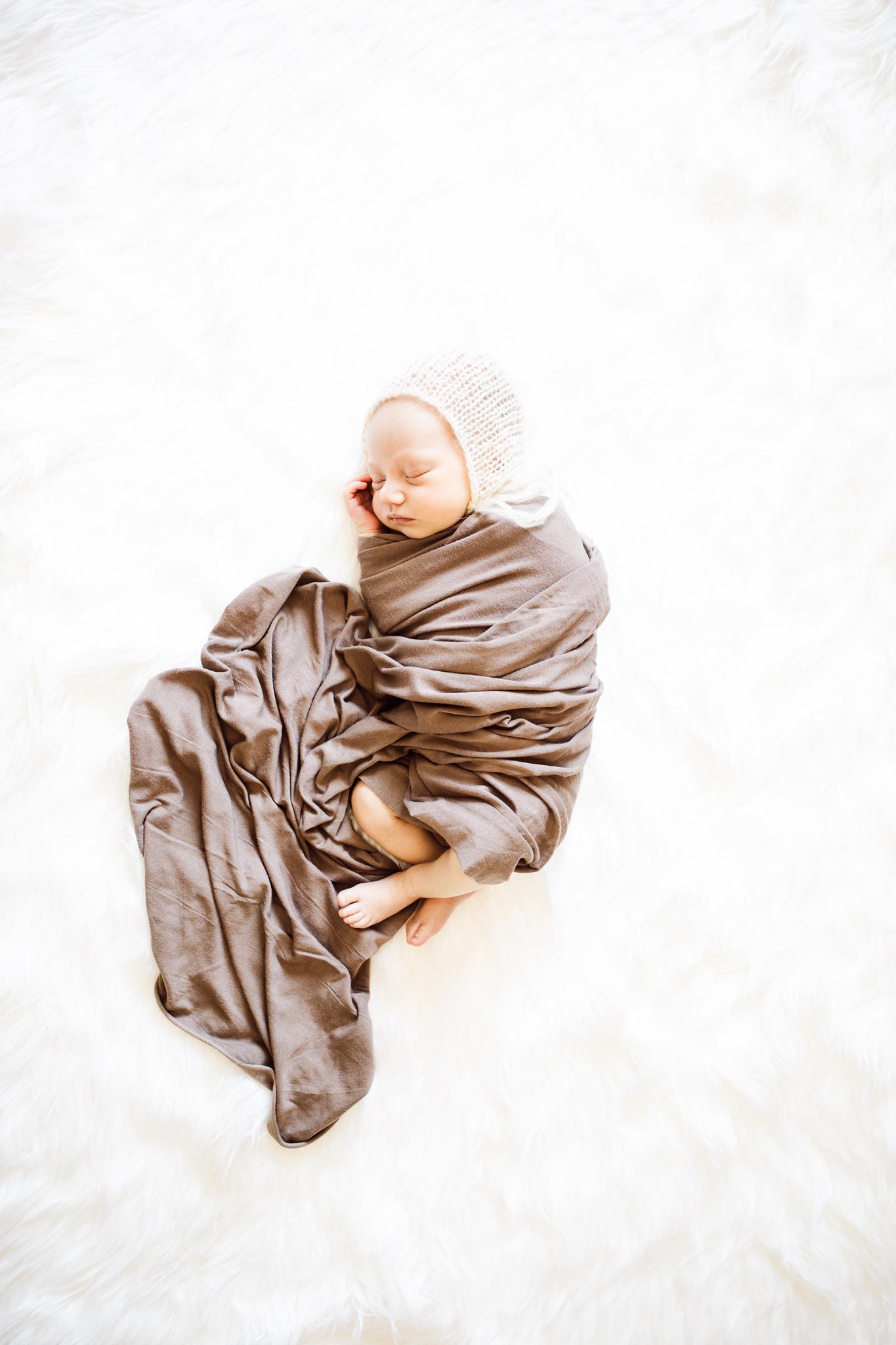 baby wrapped in brown blanket - AMG Photography