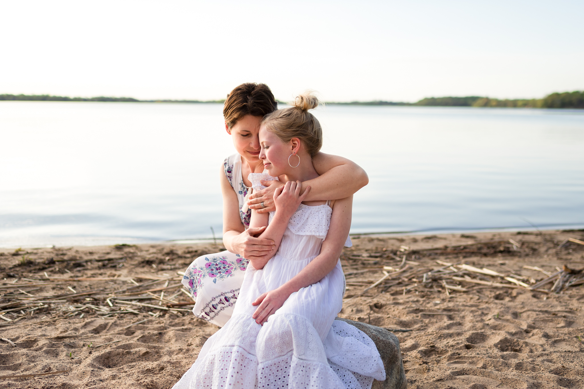 mom hugging her daughter by a lake - AMG Photography