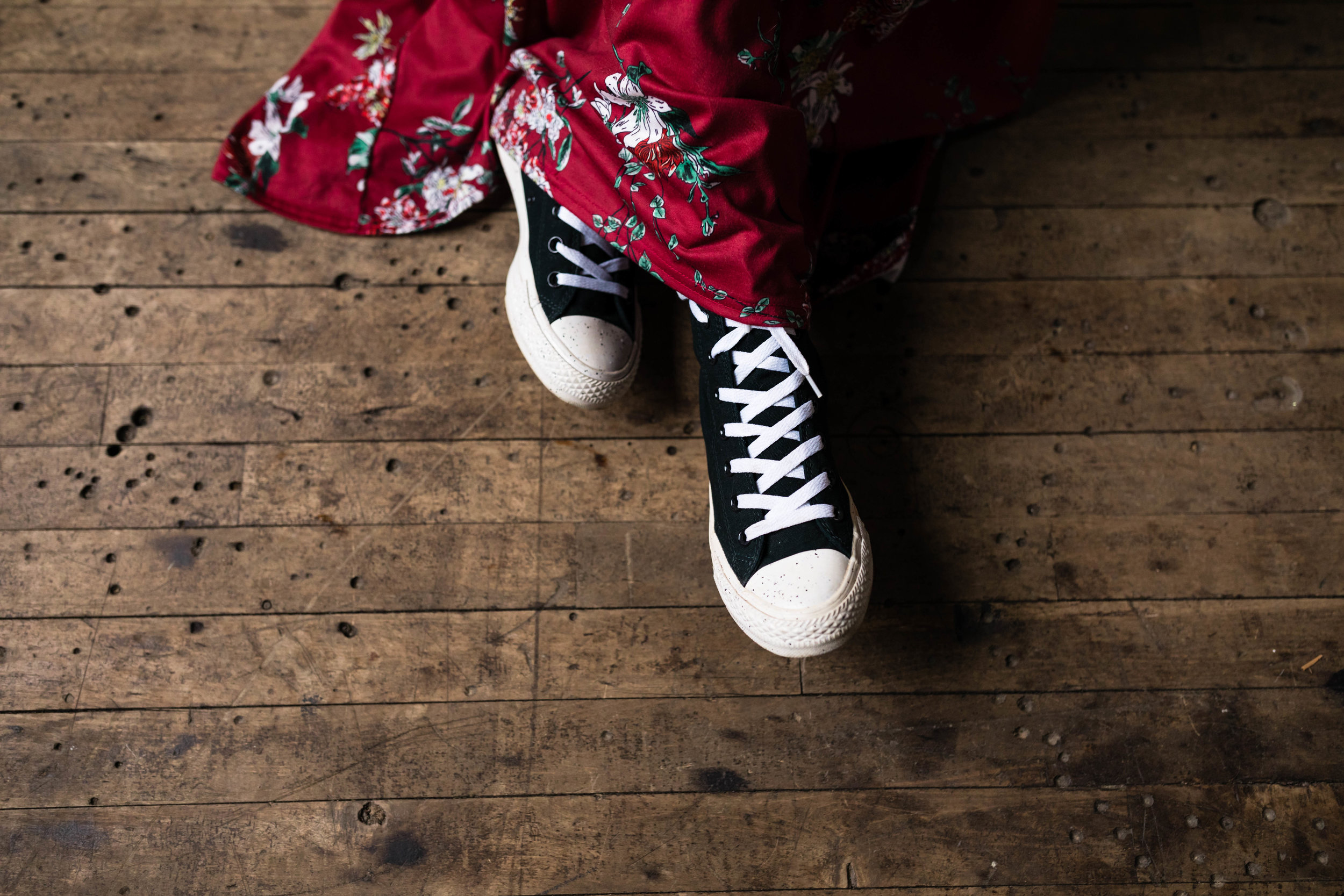 girl wearing black converse shoes with a red flowered dress