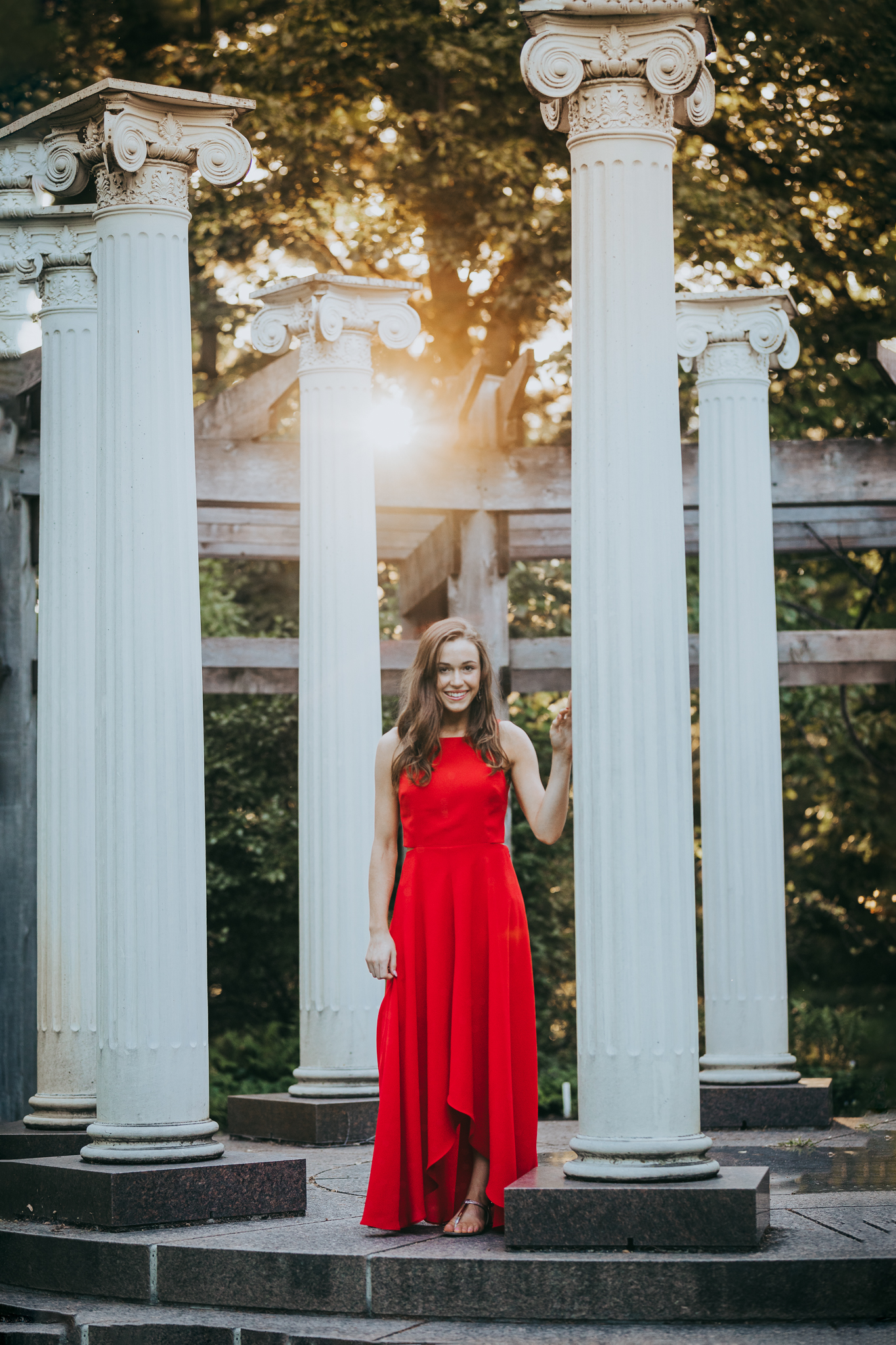 girl in red dress standing by Greek Pillars in the sunset - Wayzata High School Photographer