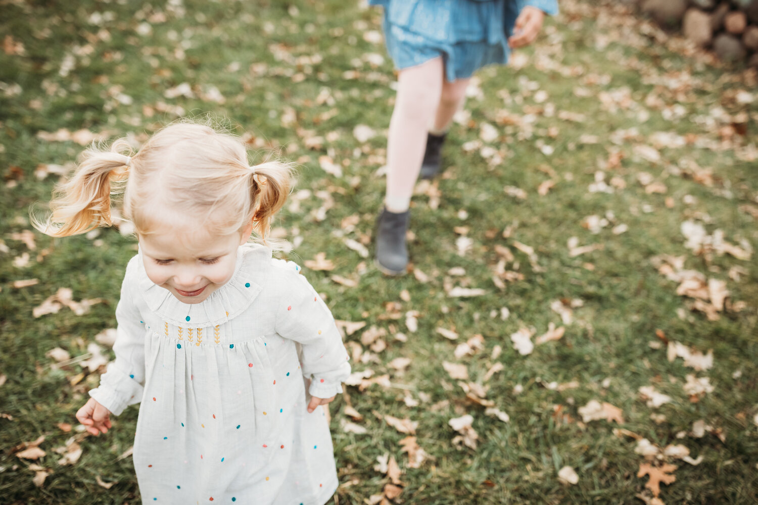 little girl in white dress with colorful polka dots running - Minnesota Family Photographer