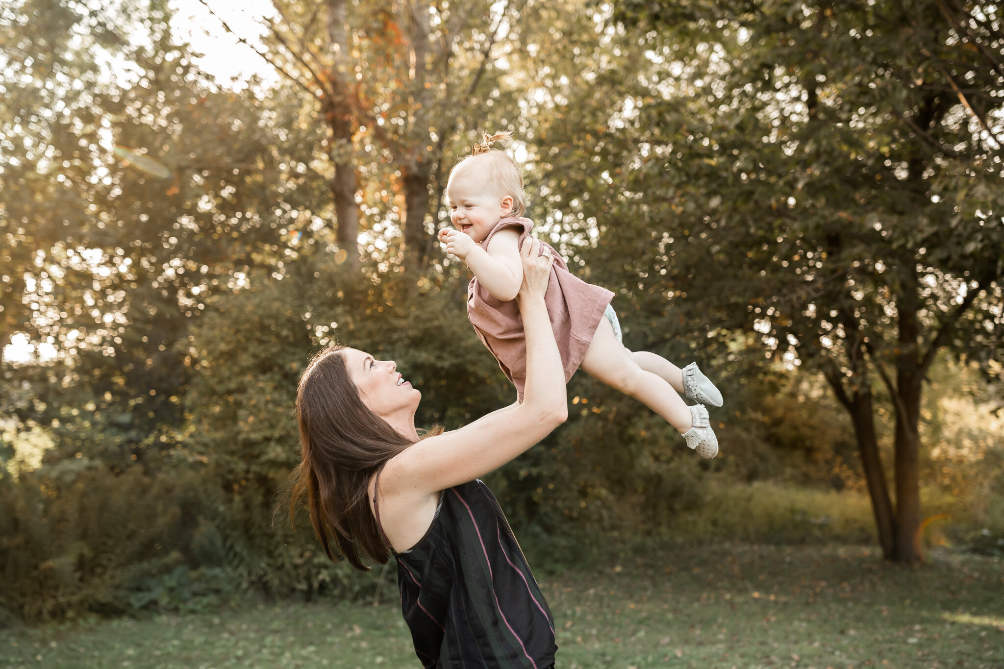 woman in black shirt holding up her baby girl laughing - AMG Photography