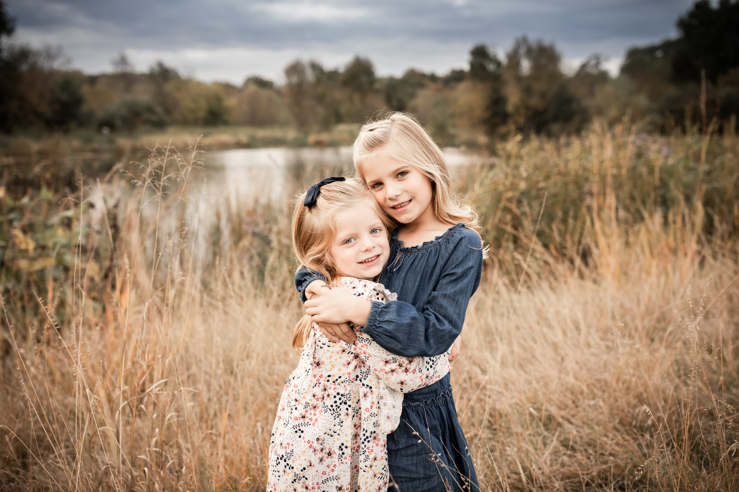 two sisters hugging in a field by a pond | Minnesota Family Photographer | AMG Photography
