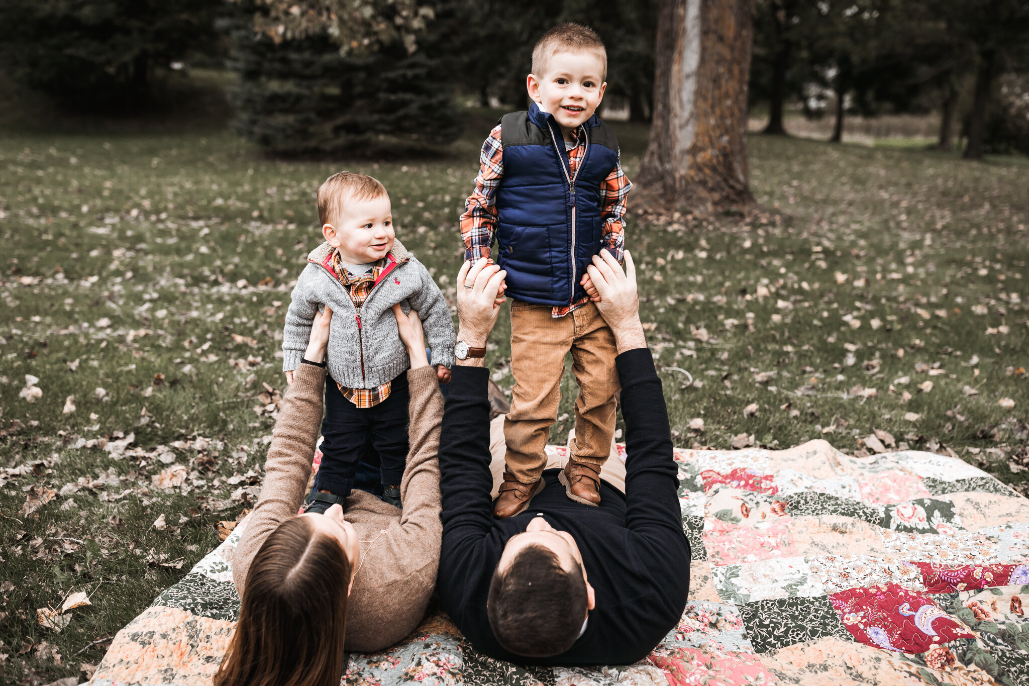 two brothers standing on top of their mom and dad in the fall leaves | AMG Photography