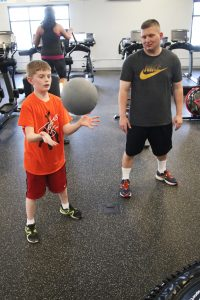 Kenny Schmidt, with his father Ken, works out with the medicine ball.