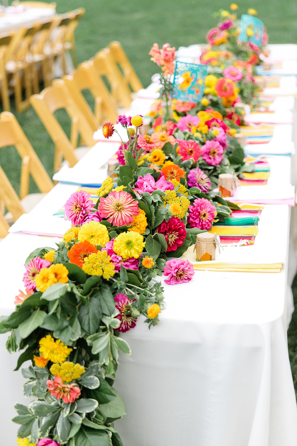 Bright zinnias in one of our weddings' lush head table garland.  Image ©   Callie Hobbs   .