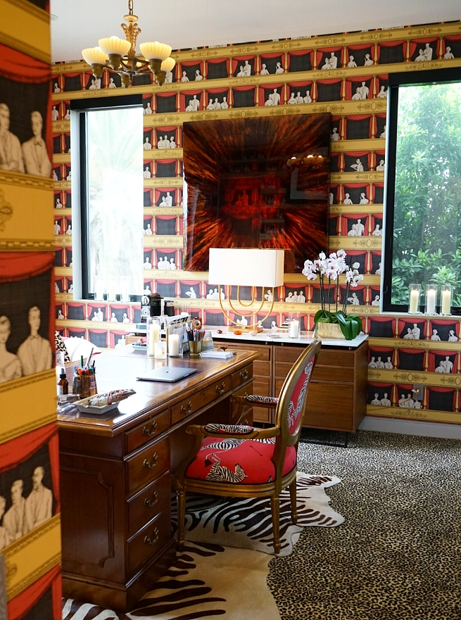 The writer's home office, which features a vintage wooden executive desk, a Nespresso machine, Fornasetti wallpaper, brass and Lucite containers, candles, sage, crystals, and a mélange of animal prints.