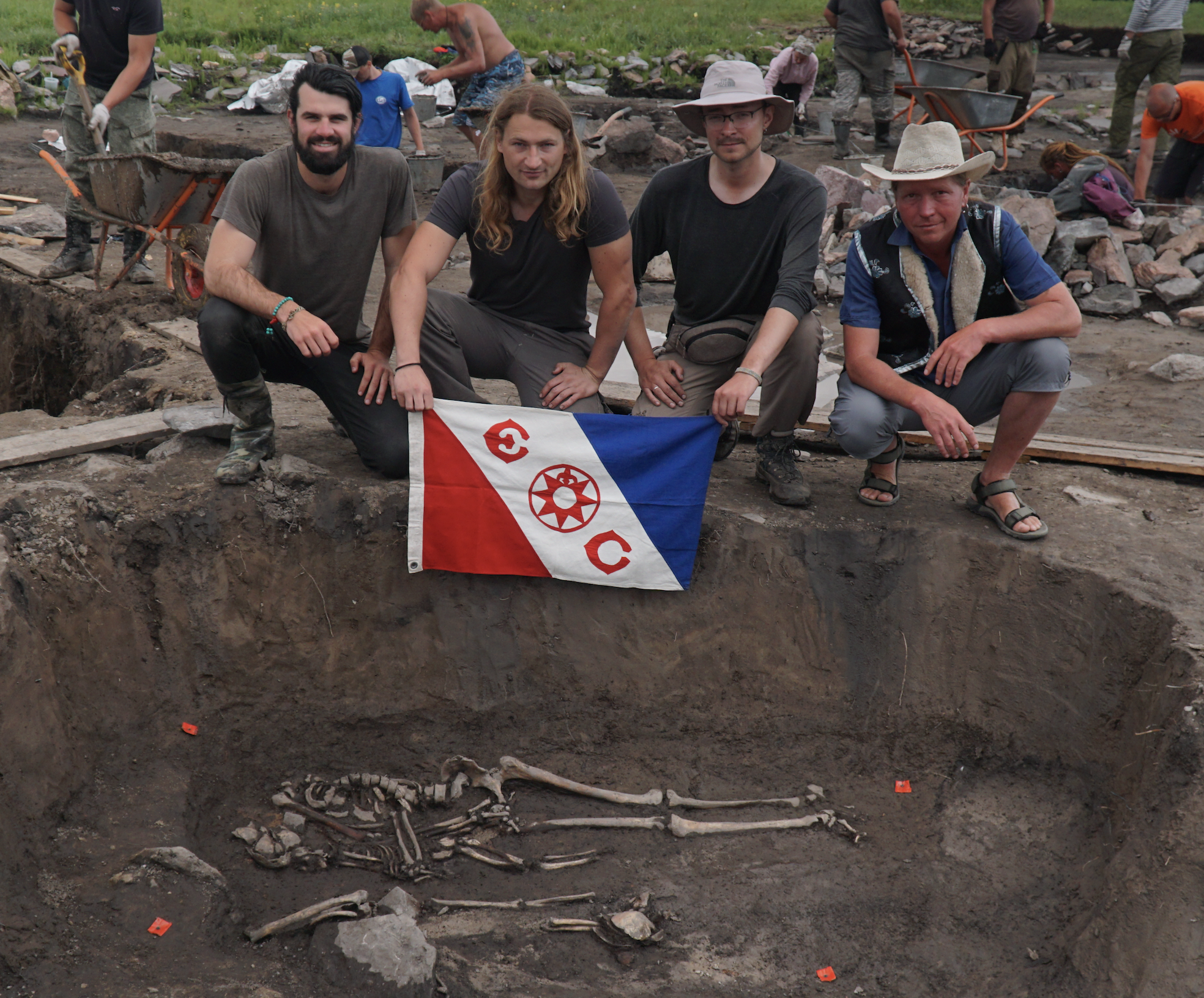 Trevor, Gino, Jegor and Timur with Explorers Club Flag #134 in front of a quadruple burial dating back 1,700 years. Here you see an adult embracing a child. They were surrounded by iron arrowheads and knives.