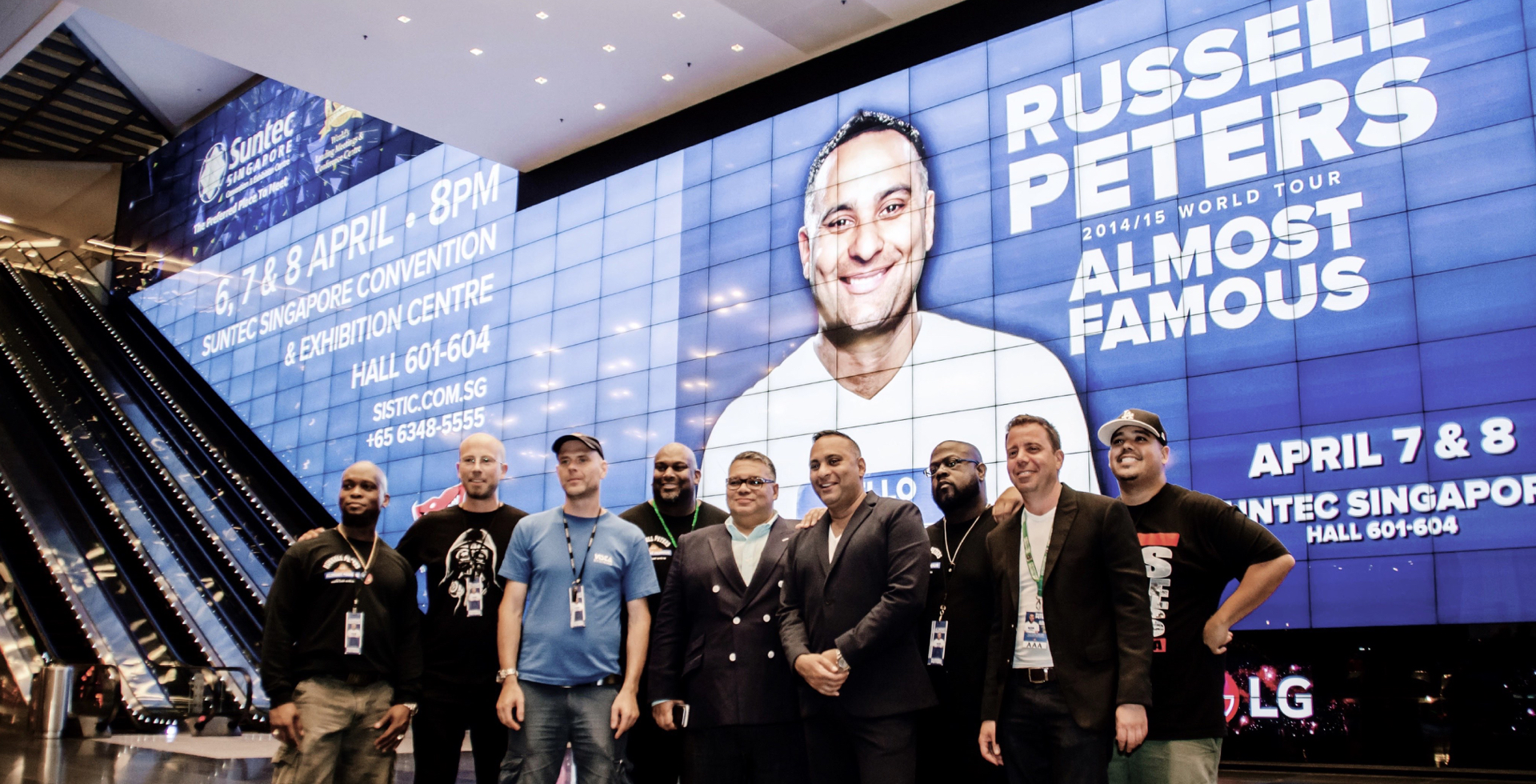 Russell Peters posing with his crew in front of his larger-than-life show image on Suntec Singapore's The Big Picture