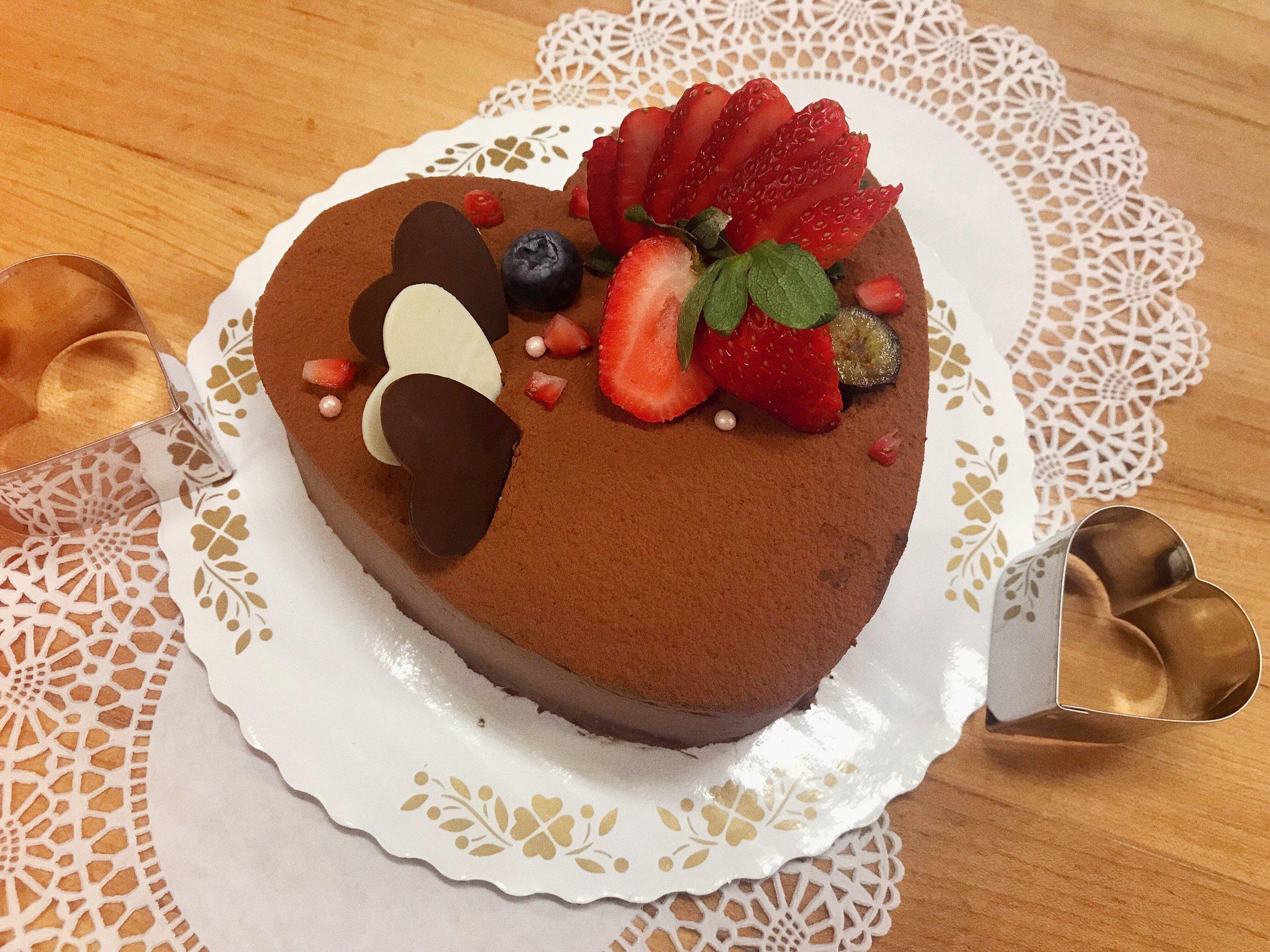"Chocolate ""Queen"" Cake - Chocolate ""Queen"" Cake - For your majesty, a moist chocolate sponge cake filled with layers of silky chocolate cream and soft chocolate sponge, generously dusted with the finest cocoa powder and topped with handmade white & milk chocolate hearts and fresh berries! 👑♥️ A delicate dessert for any chocolate lover!チョコレート 「クイーン」ケーキ:チョコをふんだんに使用したケーキとなっております。こちらのスポンジにはベルギーチョコレートを使用し、その上にしっとりとしたチョコレートクリームを重ね合わせ、仕上げに滑らかな舌触りのココアパウダーをまぶした極上の逸品となっております。付け合せに手作りホワイトチョコのハートと季節のベリーを並べてります。それは狡猾で上品な舌触りですがその中でゆっくりと姿を現す繊細な甘さはまるで恋慕に浸る情炎な女王様を彷彿とさせる上品でしっとりしたチョコレートケーキとなっております。"