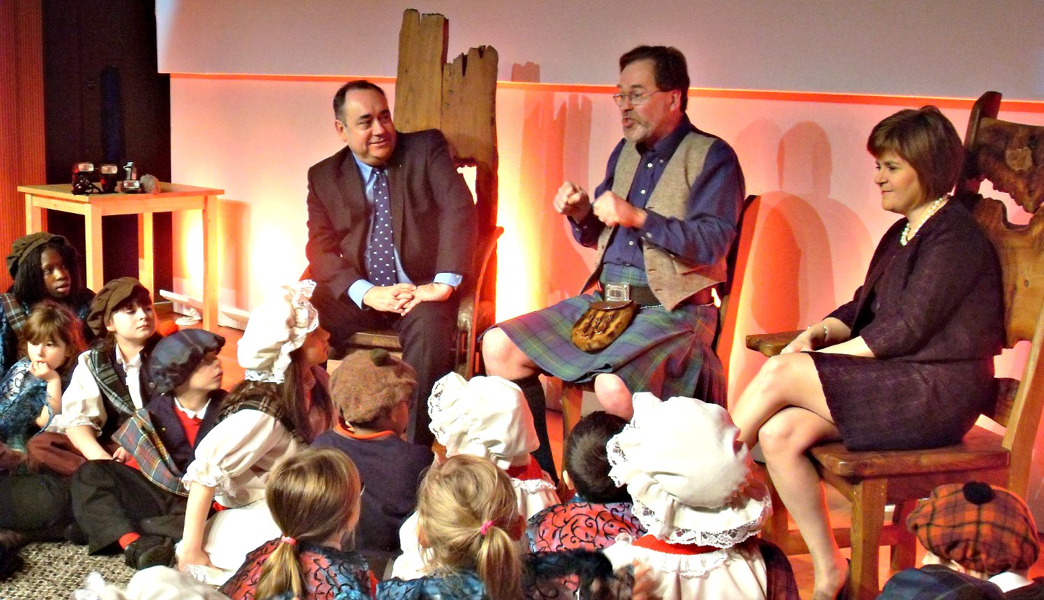 Donald Smith tells tales of Robert Burns to Royal Mile Primary School children. Senior figures of the Scottish National Party, Alex Salmond and Nicola Sturgeon, listen in. Credit: Lindsay Corr.