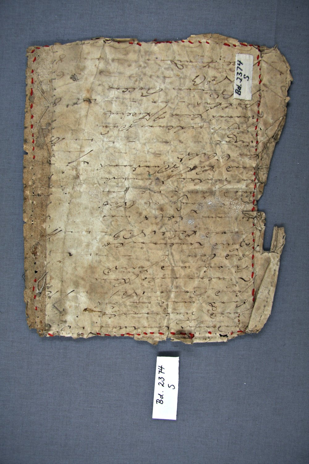 """A document visible on the back side of a """"brøstduk"""", for stiffening and perhaps also as a secret or memory."""