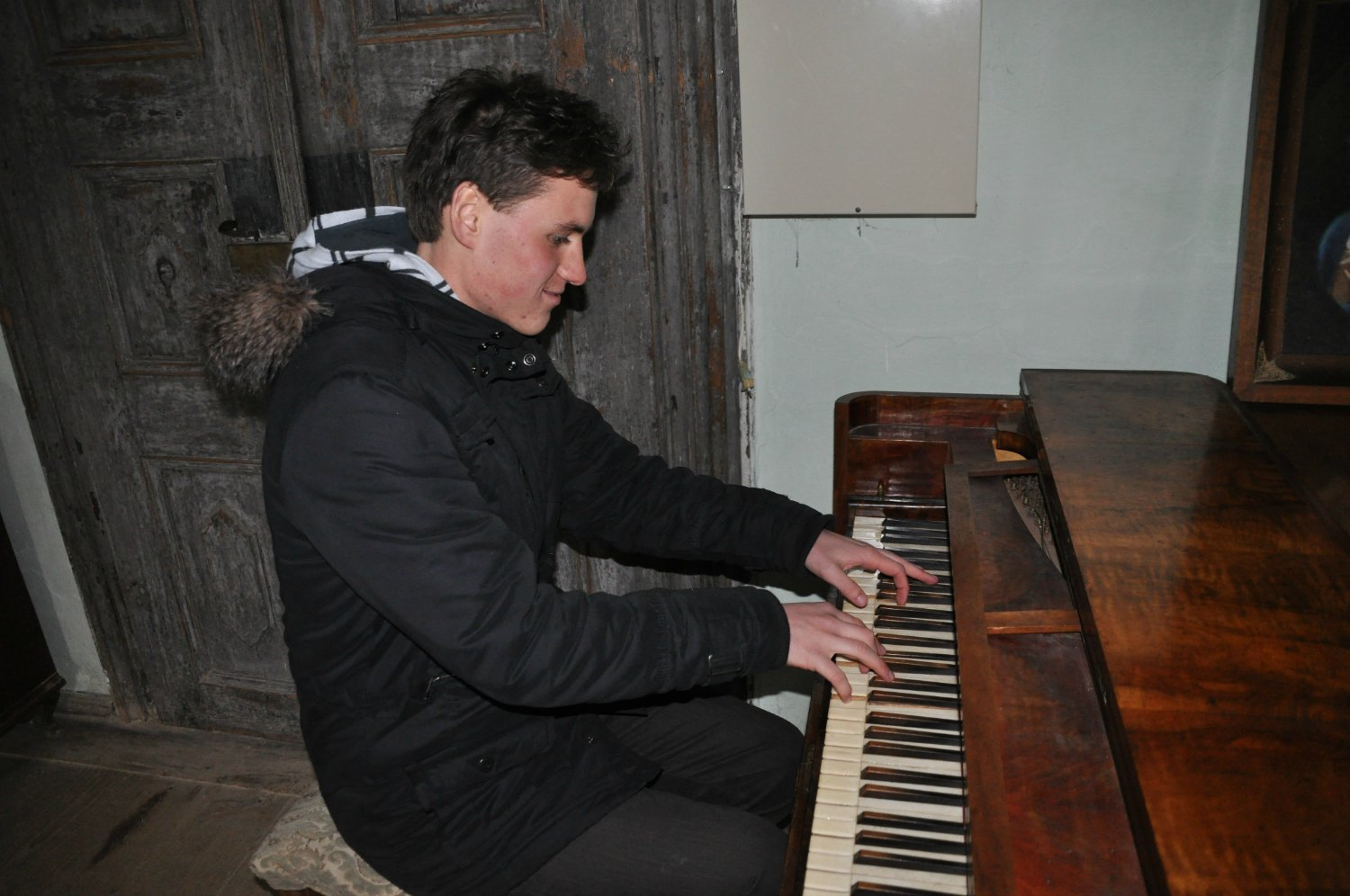 Vito playing a tune on an antique piano.