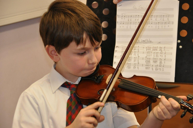 A Glasgow Gaelic School pupil practices the violin. Photo: Meg Pier