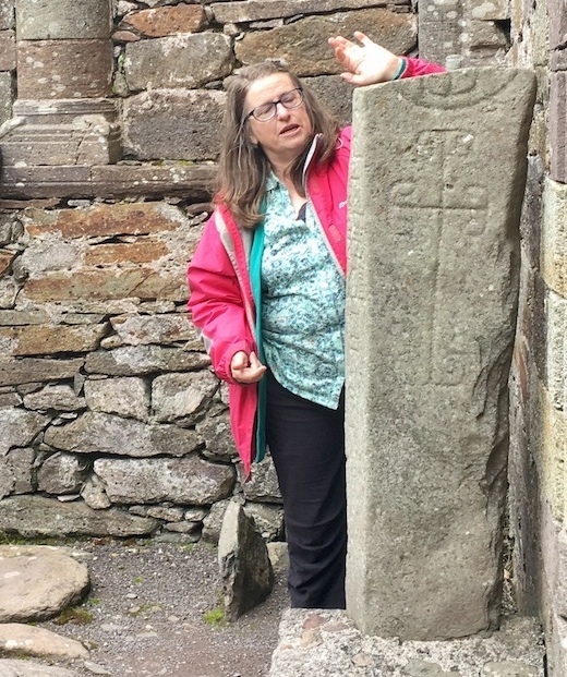 Archaeologist Isabel Bennett with a stone inscription. Photo credit: Isabel Bennett