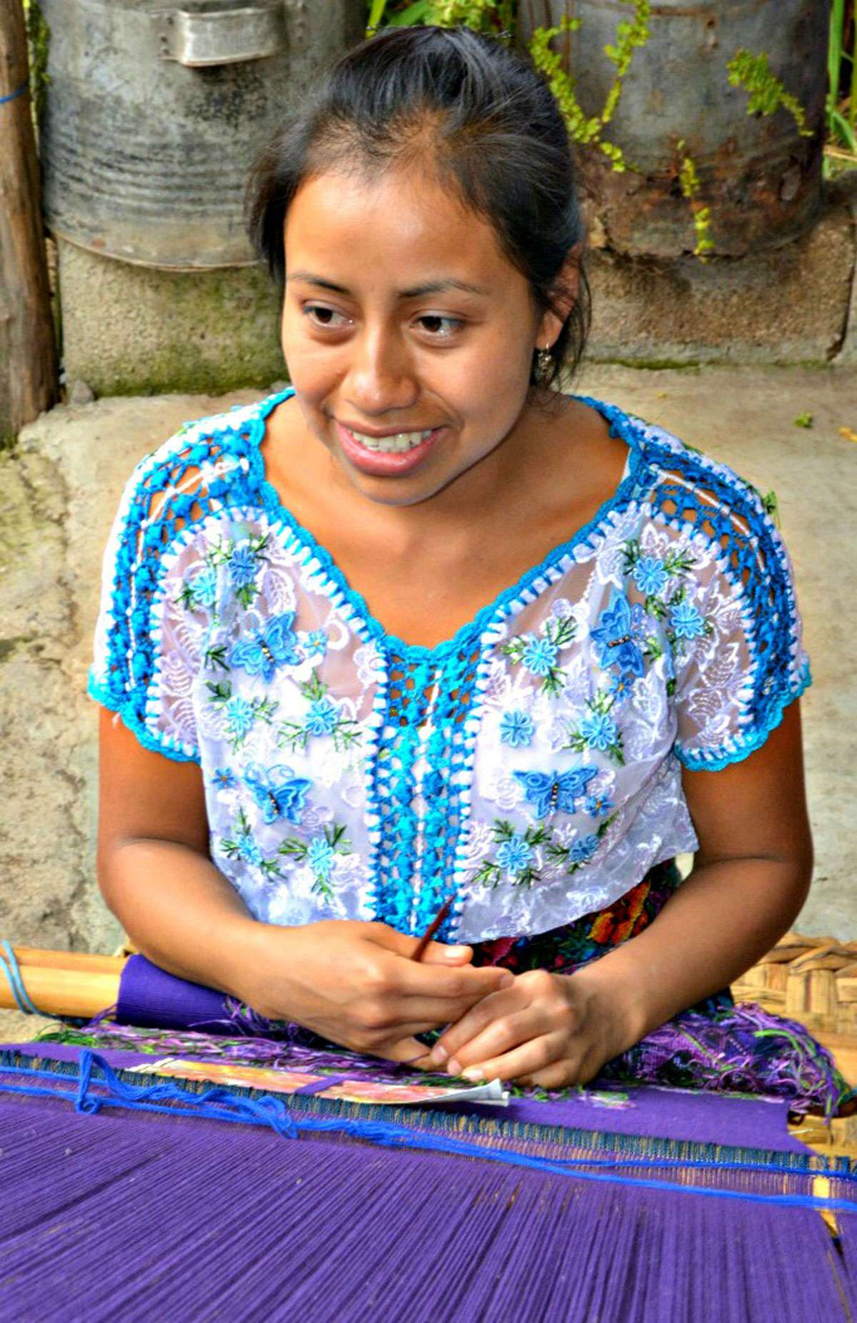 Sandy demonstrating the back strap loom and the traditional way of hand weaving garments. Photo: Meg Pier
