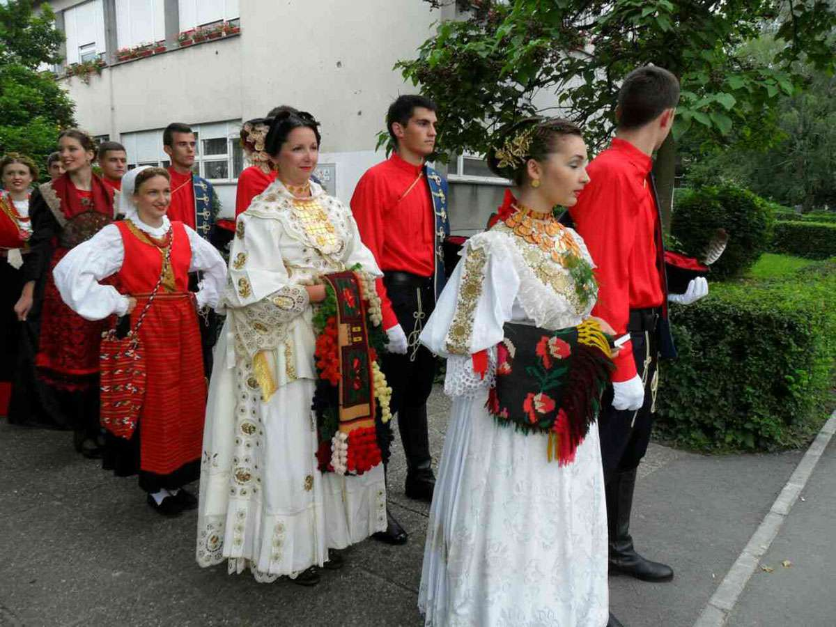 "Mirela Mrvelj of Bicko Selo dresses for a folk dance performance with the assistance of local priest Mato Knežević. To create the ""kika"" hairstyle can take up to two hours, and putting on a folk costume can take four hours."