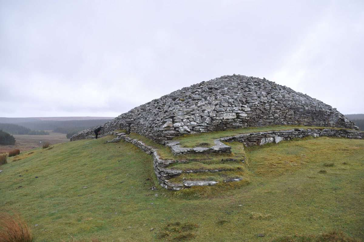 The figure on the left of the cairn gives a sense of the size of the structure. Photo: Meg Pier
