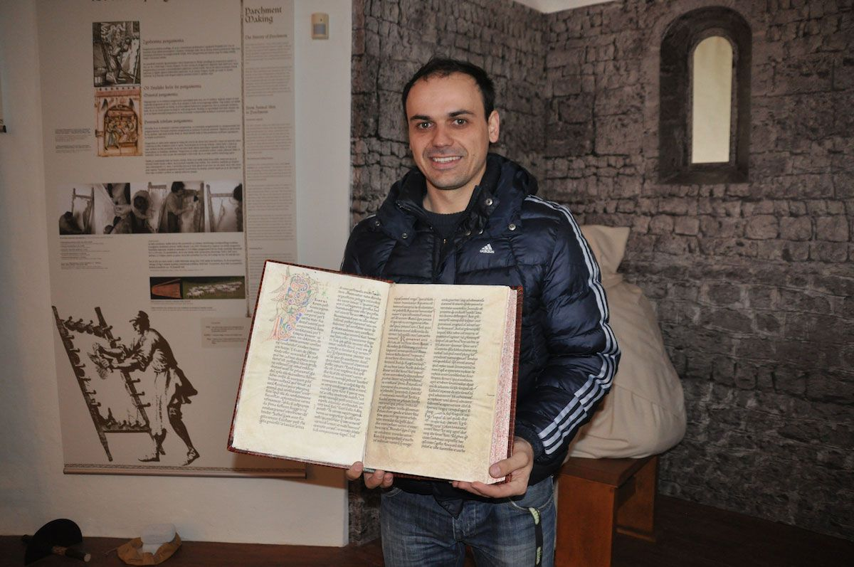 Tadej displaying some of the ancient texts recorded by Monk scribes. Photo: Meg Pier