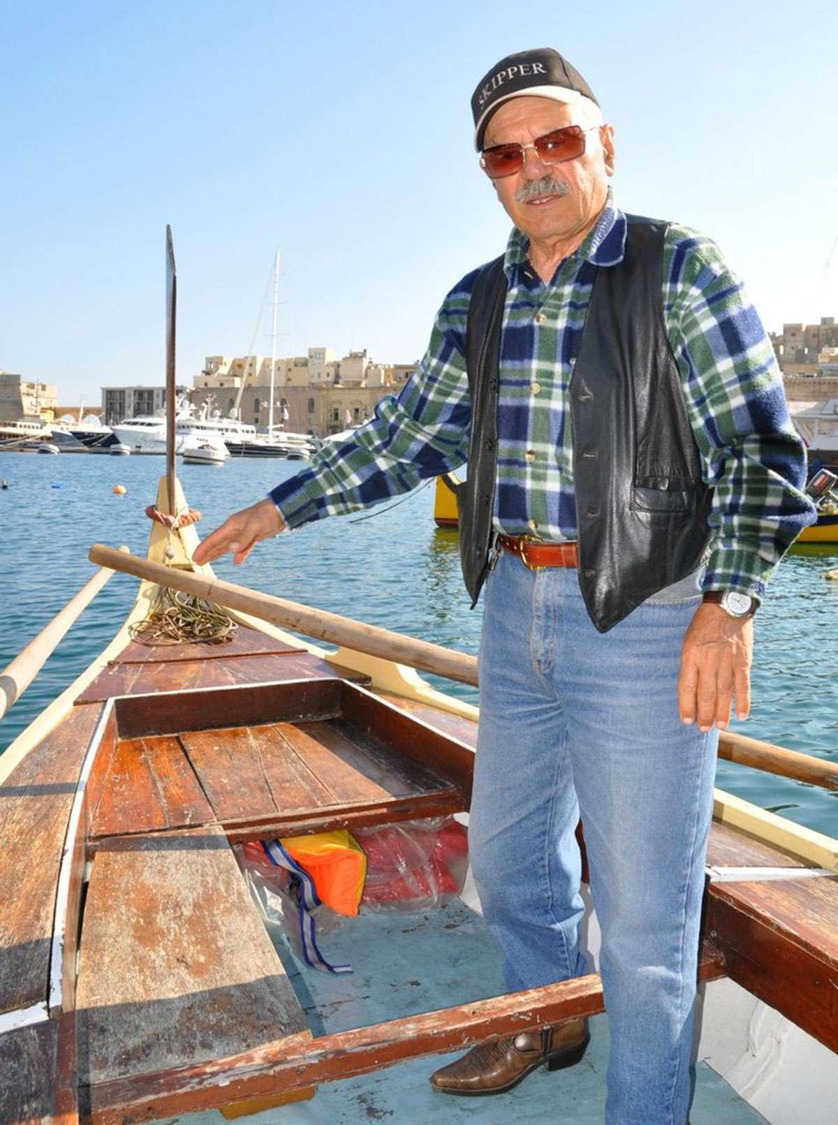 Boatman Carmen Farrugia steers his dghajsa toward Vittoriosa's Maritime Museum