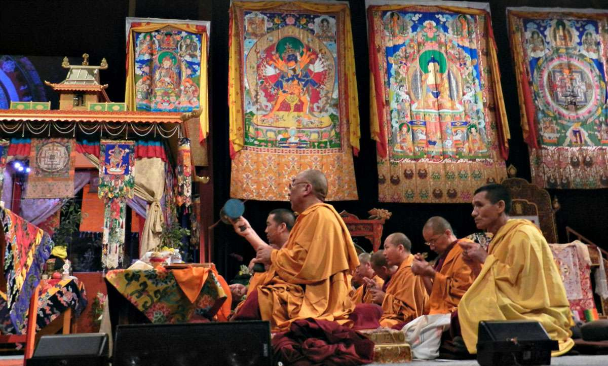 Tibetan Buddhist Khenpo leading lamas in offerings to the deities, facing the Kalachakra pavilon, Thankgas of Padmasambhava, Kalachakra, Buddha, Kalachakra Mandala, Verizon Center, Washington D.C., USA : Photo:  Wonderlane