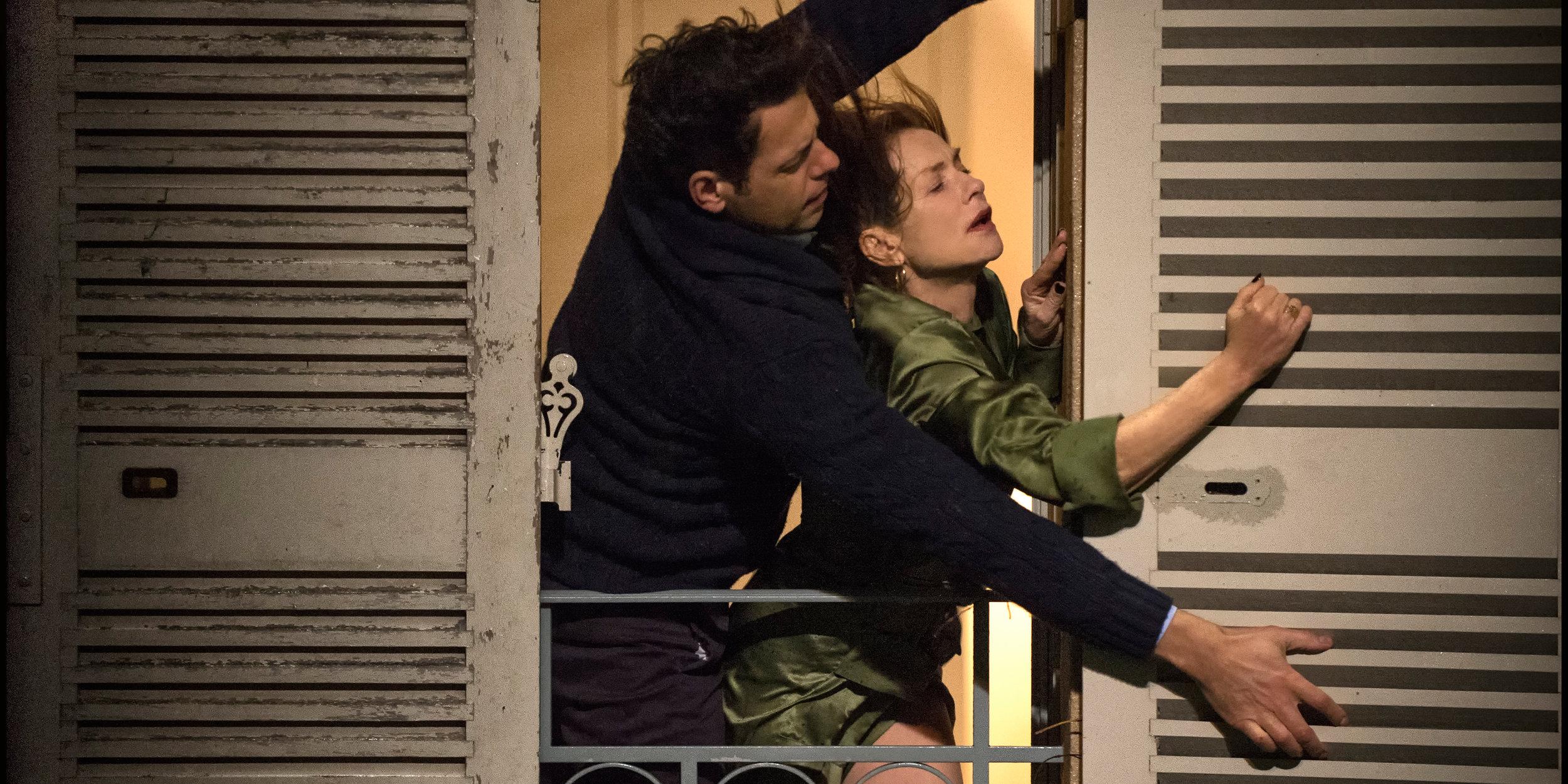 Den enslige   Michèle  (Isabelle Huppert) får hjelp av den tiltrekkende naboen til å lukke vinduslemmene i en storm.