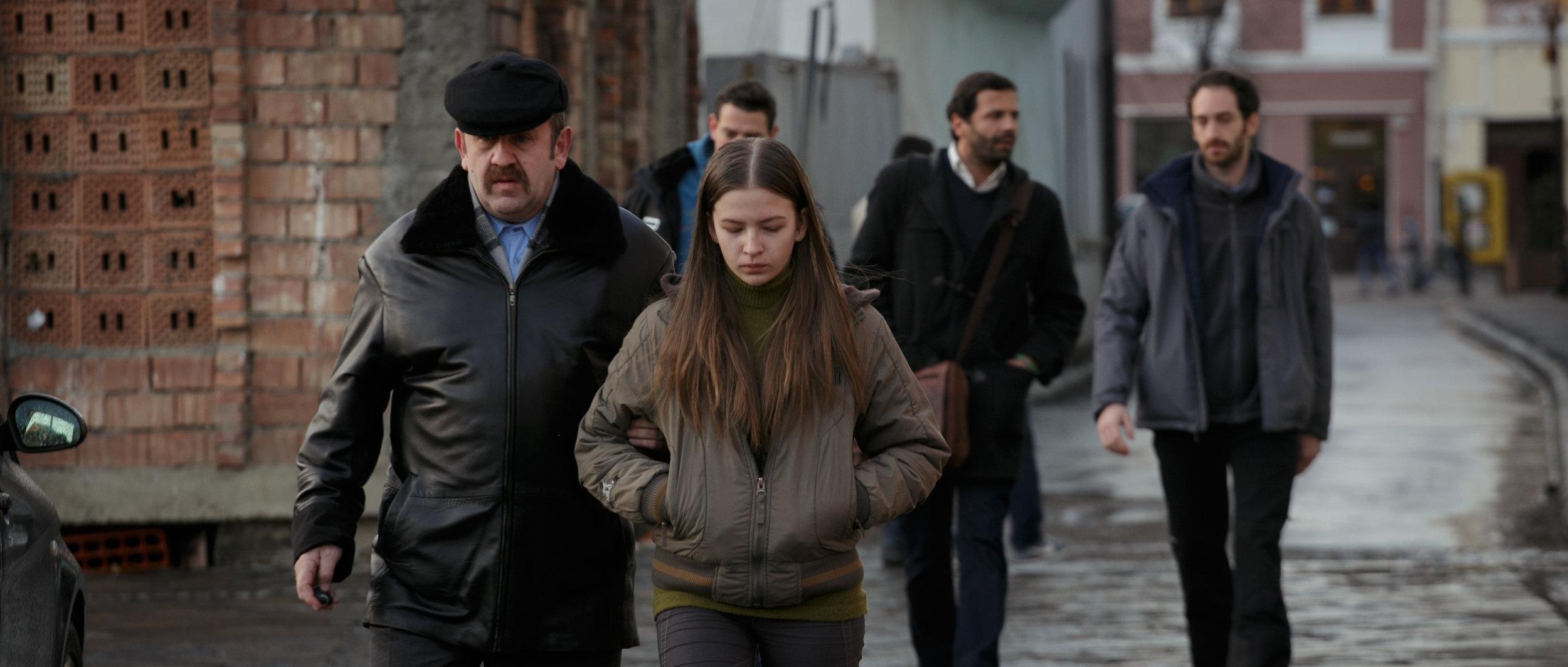 Tilbake igjen i Romania geleides Anca av politisjefen som vil la henne bli intervjuet av tv-teamet i bakgrunnen.