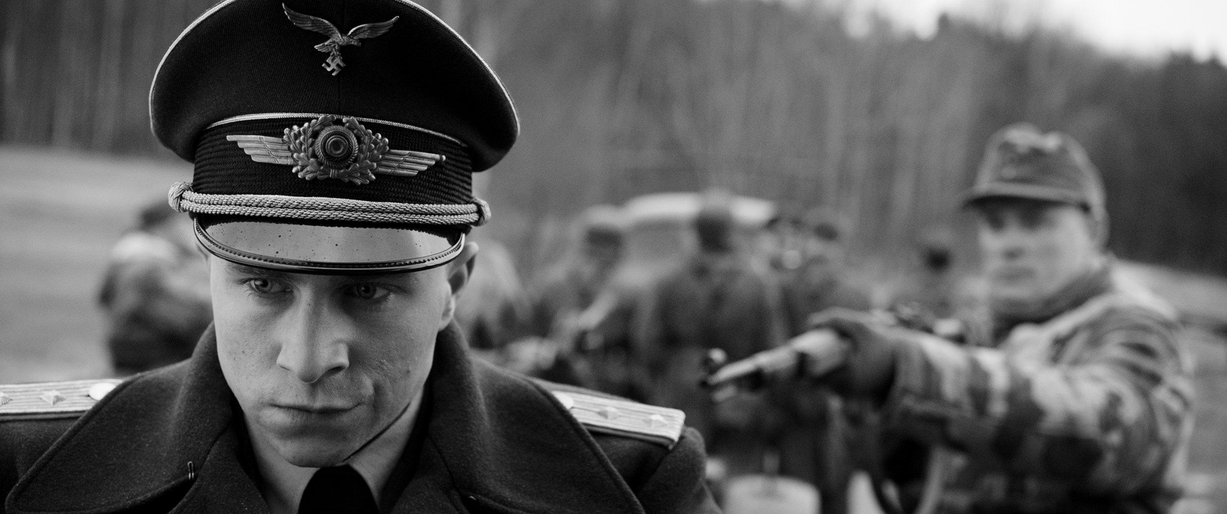 Militære som støter på desertøren Willy Herold (Max Hubacher), lar seg raskt lure. Kapteinsuniformen han har tatt på seg, gir ham et nytt utseende og en ny autoritet. (Foto: Many More Films)
