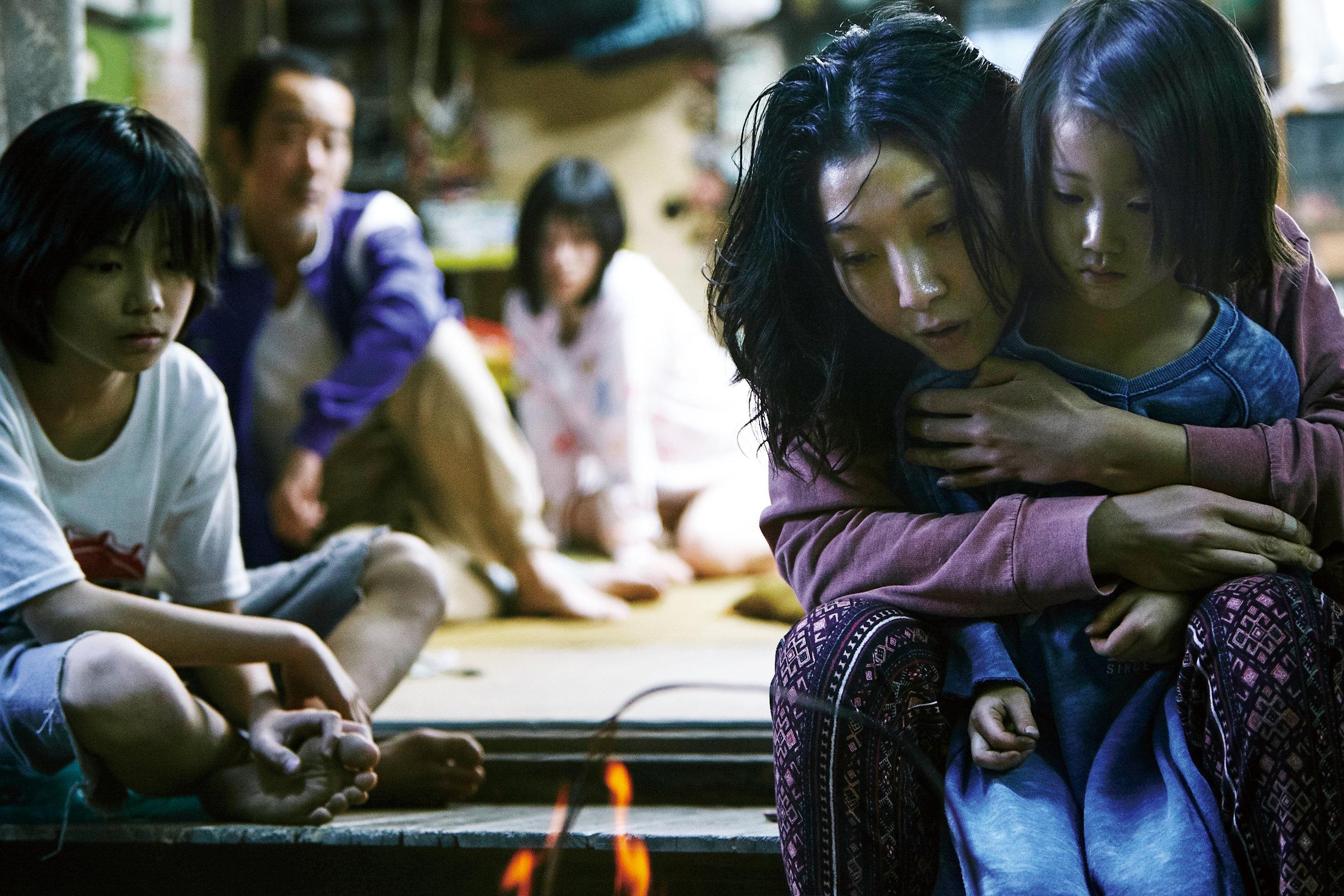 At barn kan ha det godt hos voksne som ikke er deres biologiske foreldre, er et tema Hirokazu Kore-eda er opptatt av. Til høyre tar Nobuyo (Sakura Andô) seg av den forsømte jenta Yuri (Miyu Sasaki). Til venstre sitter Shota (Jyo Kairi) og bak ham familiens farsfigur Osamu og den vakre Aki.
