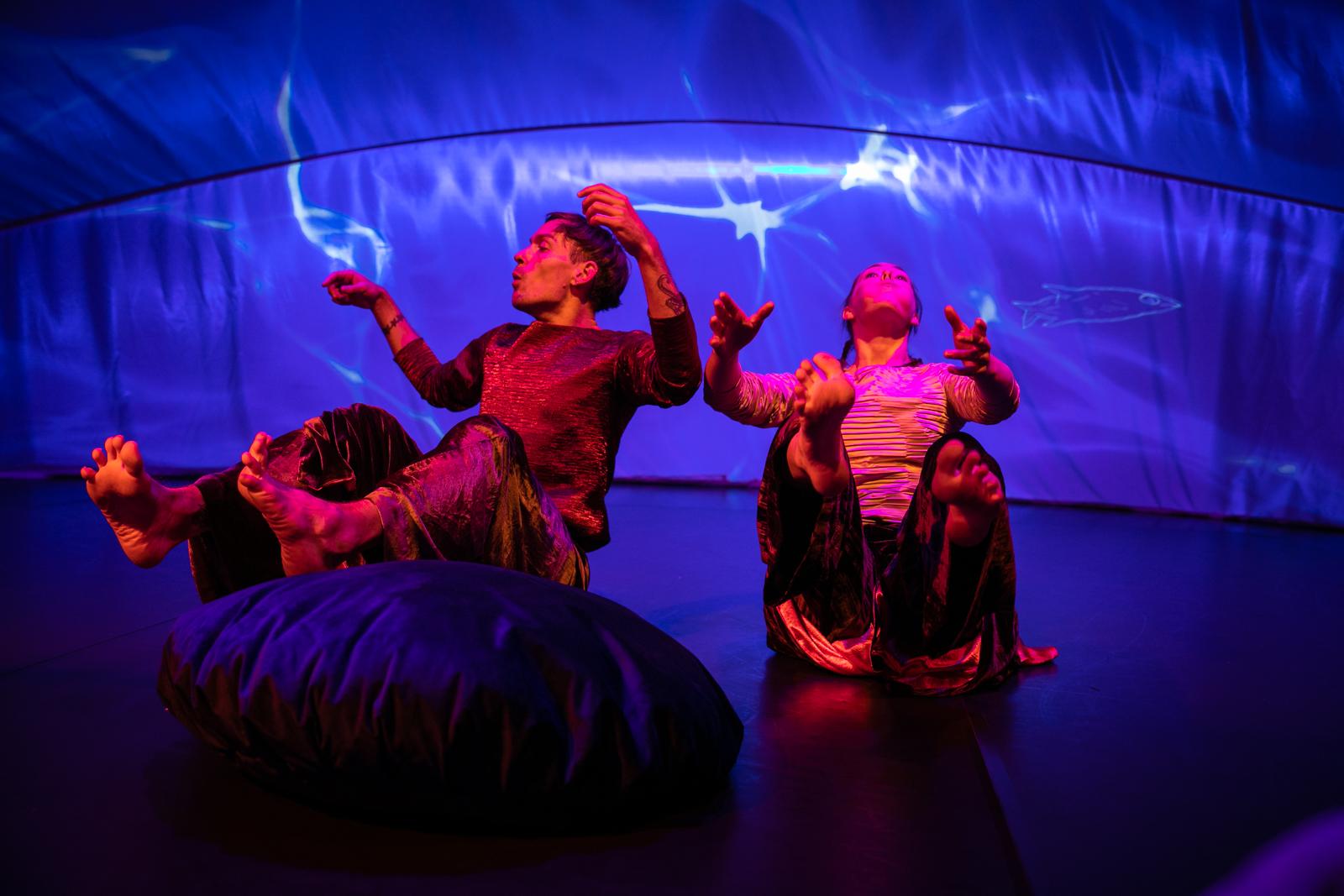 Danserne Gerd Elin Aase og Luke Birch som fisker i forestillingen Rarere. På slørveggen bak projiseres animasjoner av Per Dybvig.