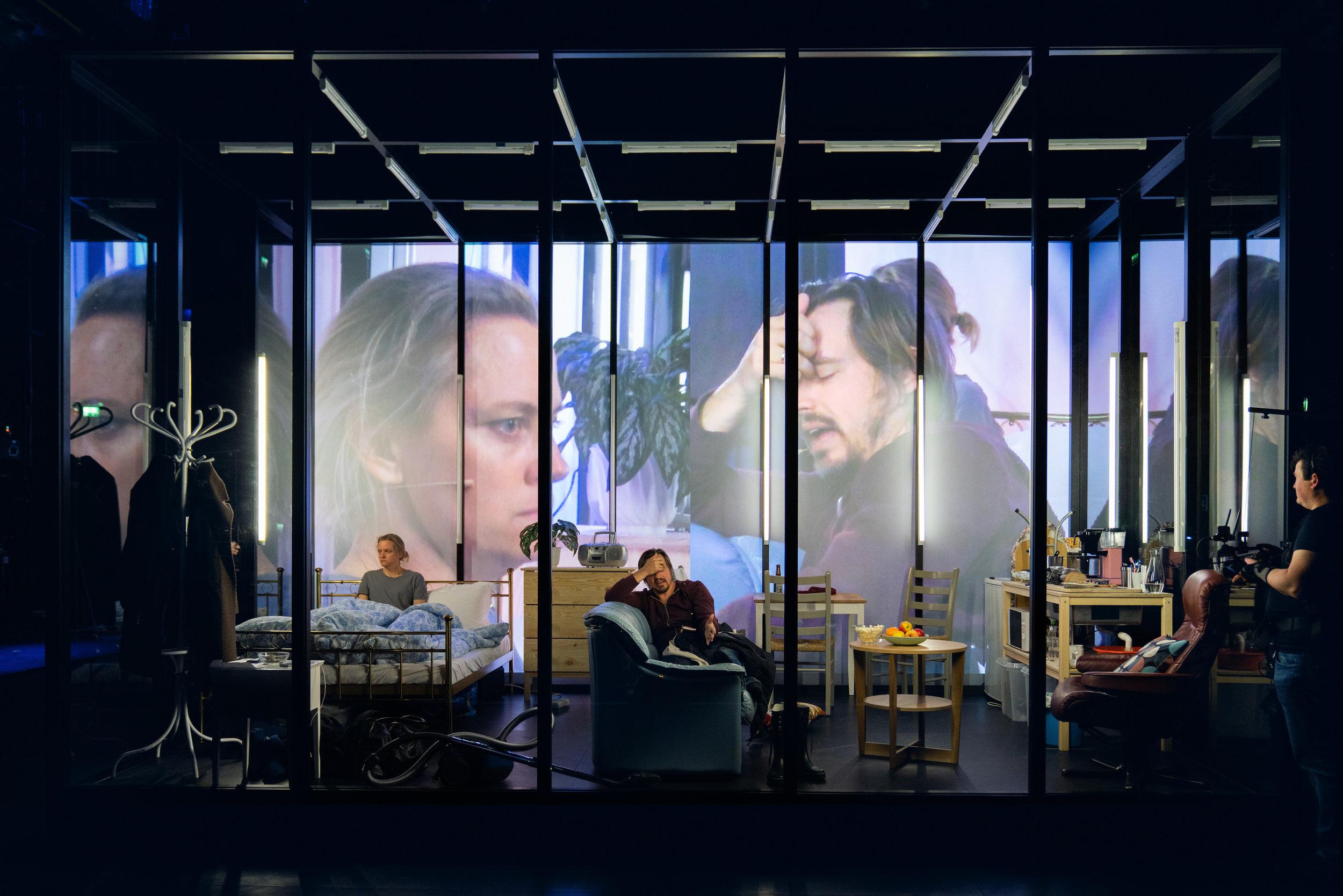 To kameramenn filmer skuespillerne inni et glassbur. Ansiktene til Nina Ellen Ødegård og projiseres på burets 3,5 meter høye indre langvegg slik at vi se hvordan Marianne og Johan reagerer på hverandre. (Foto: Stig Håvard Dirdal, Rogaland teater)