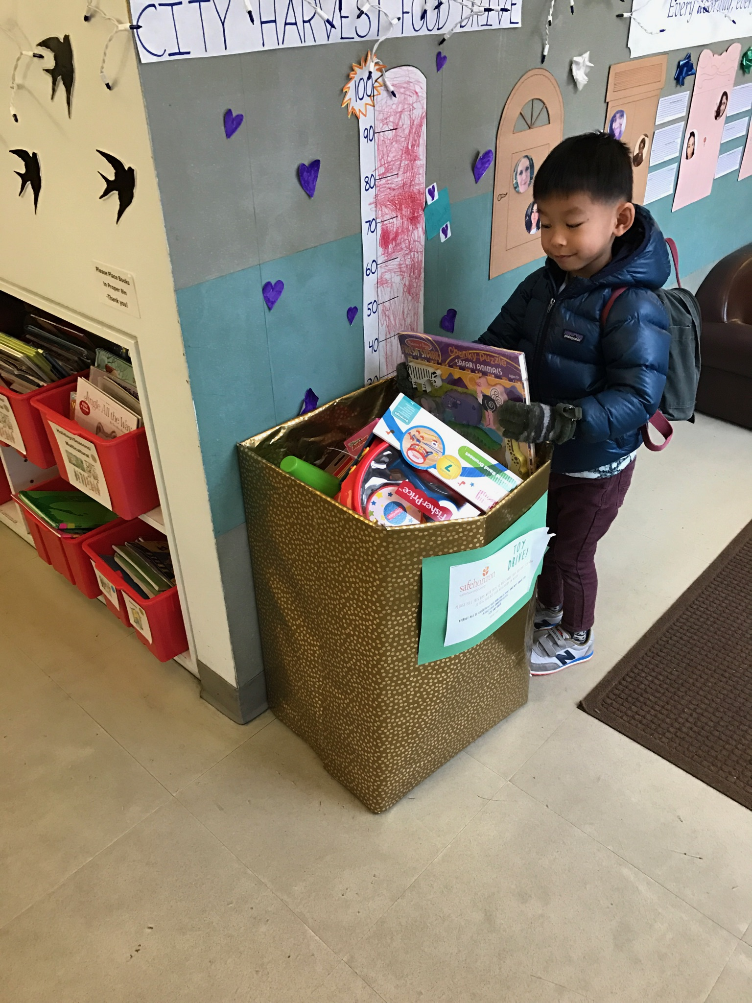 A student makes his donation to our Safe Horizon Toy Drive.