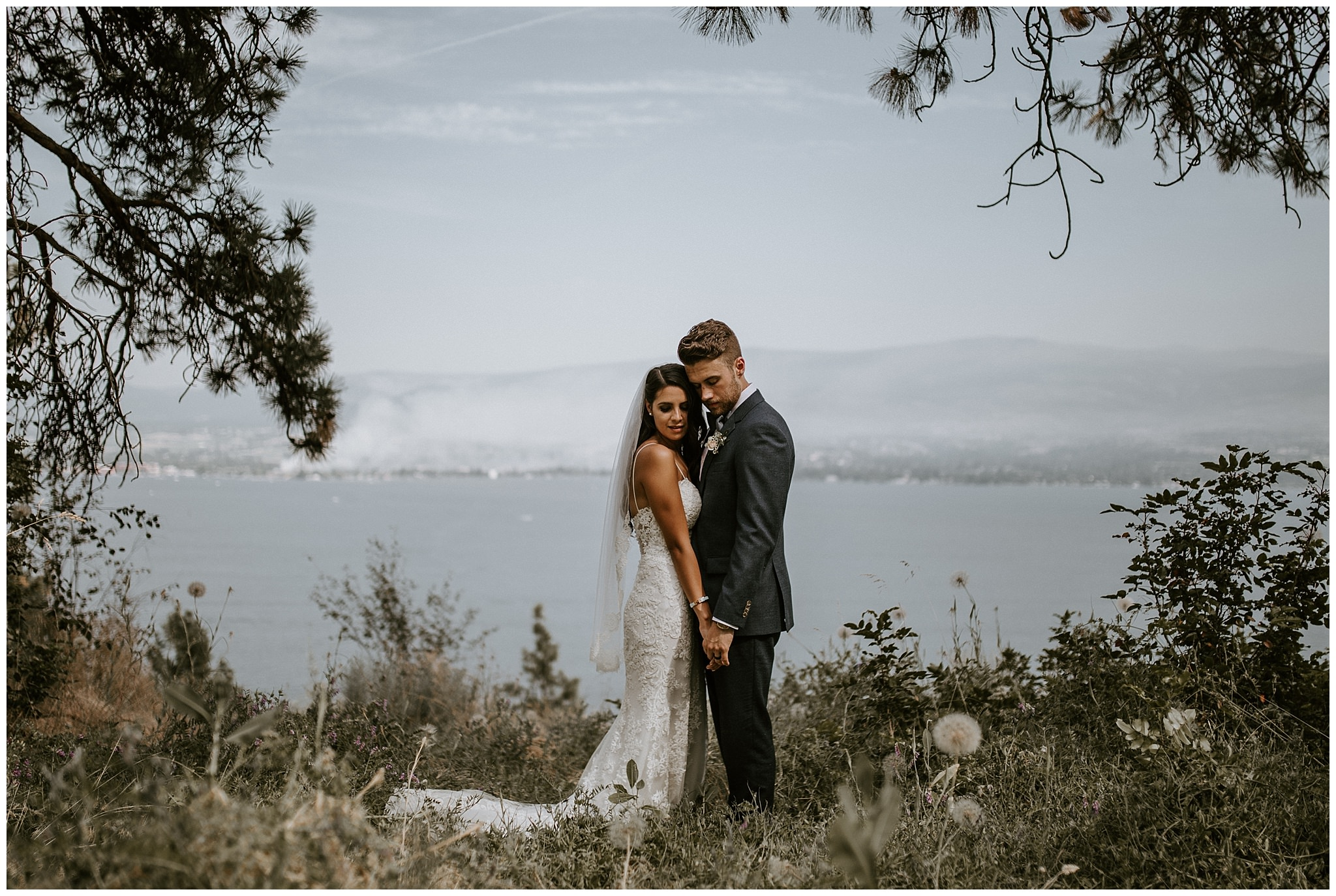 A bride and groom in front of a view of Okanagan Lake