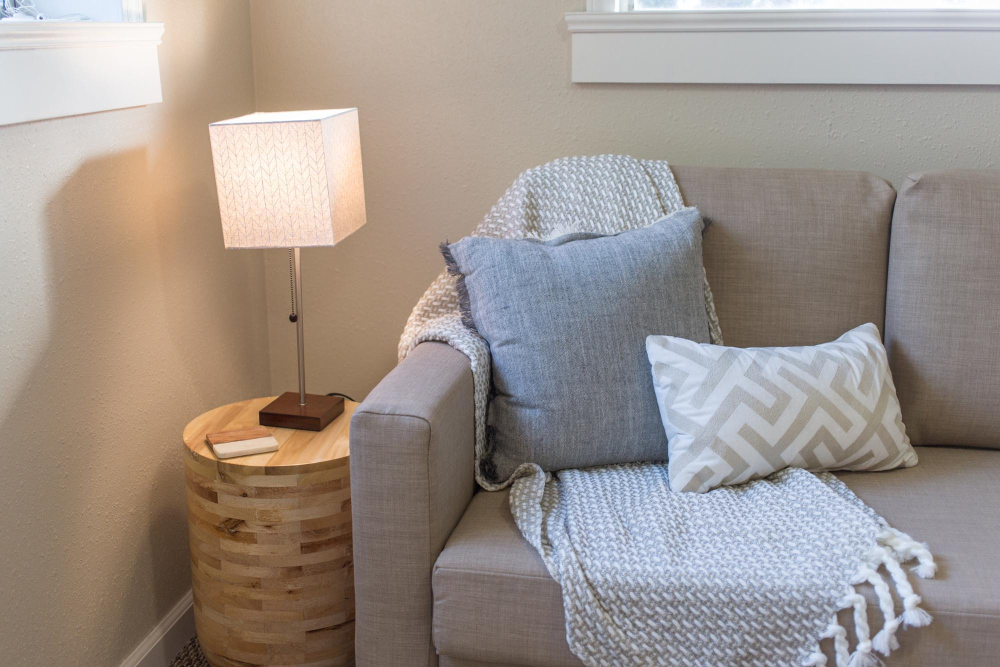 Soft grey sofa with pillows, side table and lamp