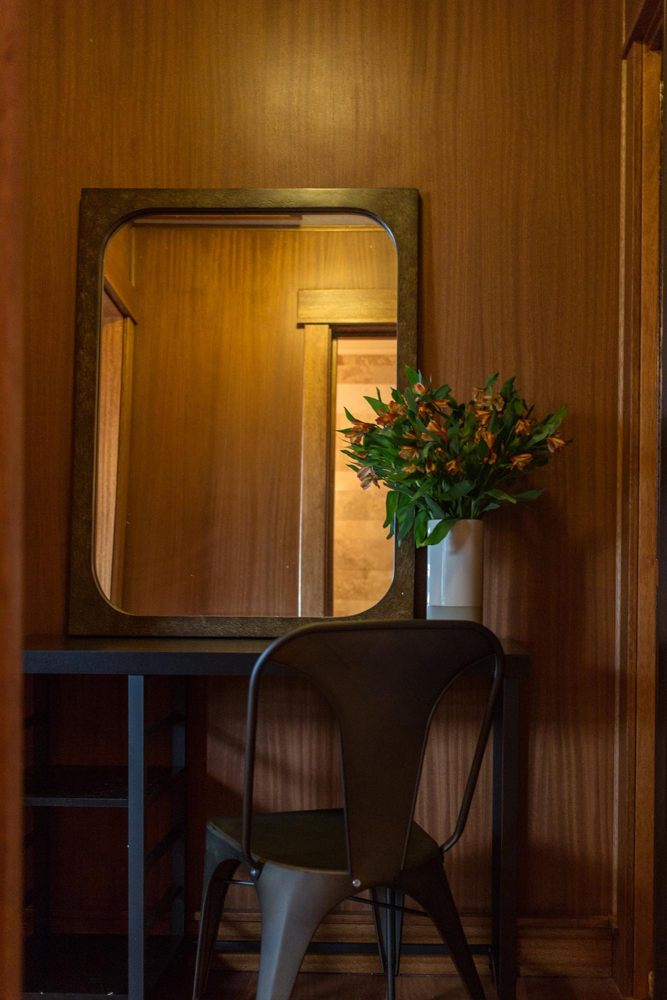 Small desk with chair, mirror and flowers