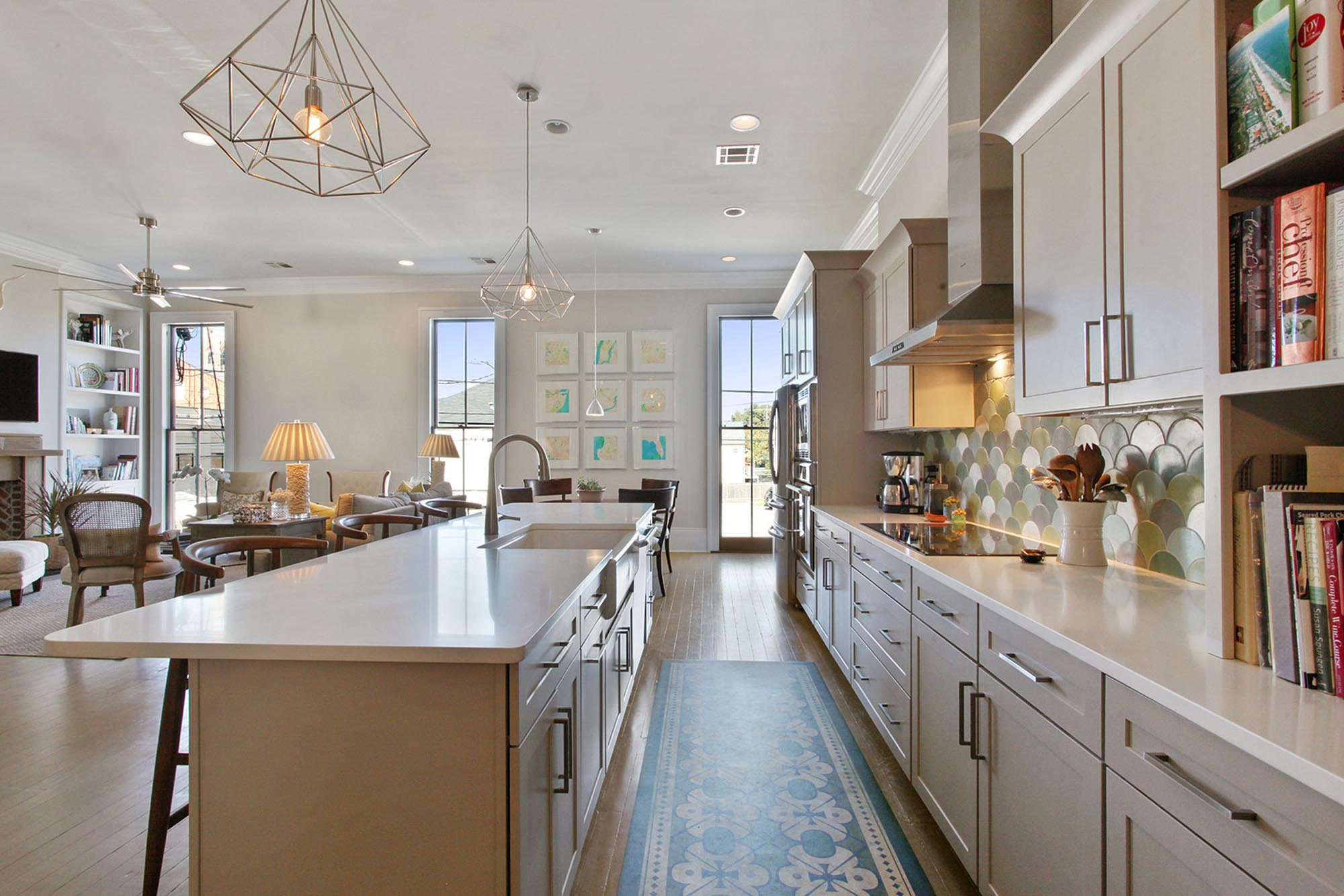 Long kitchen island with geometric hanging metal light fixture above