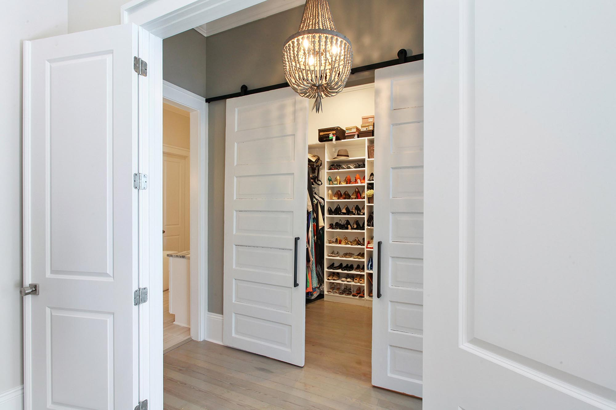 Walk in closet with wood empire chandelier