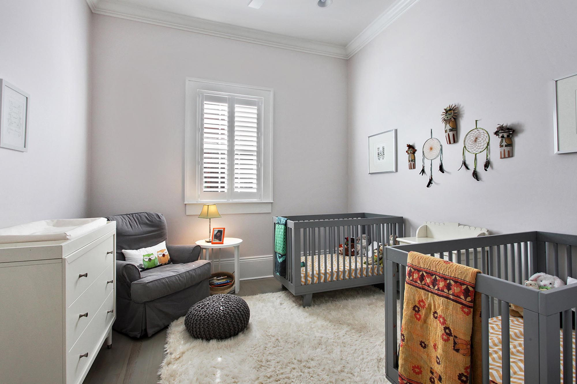 Bright twins' nursery with two grey painted cribs