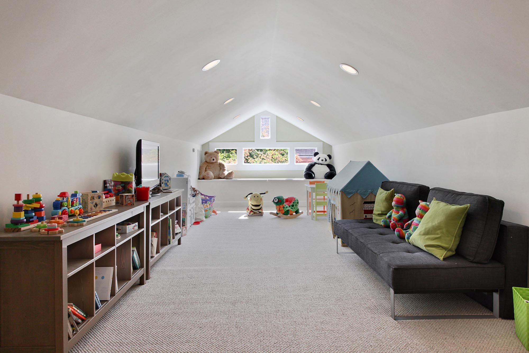 Large attic loft with children's toys on shelves and a guest futon bed