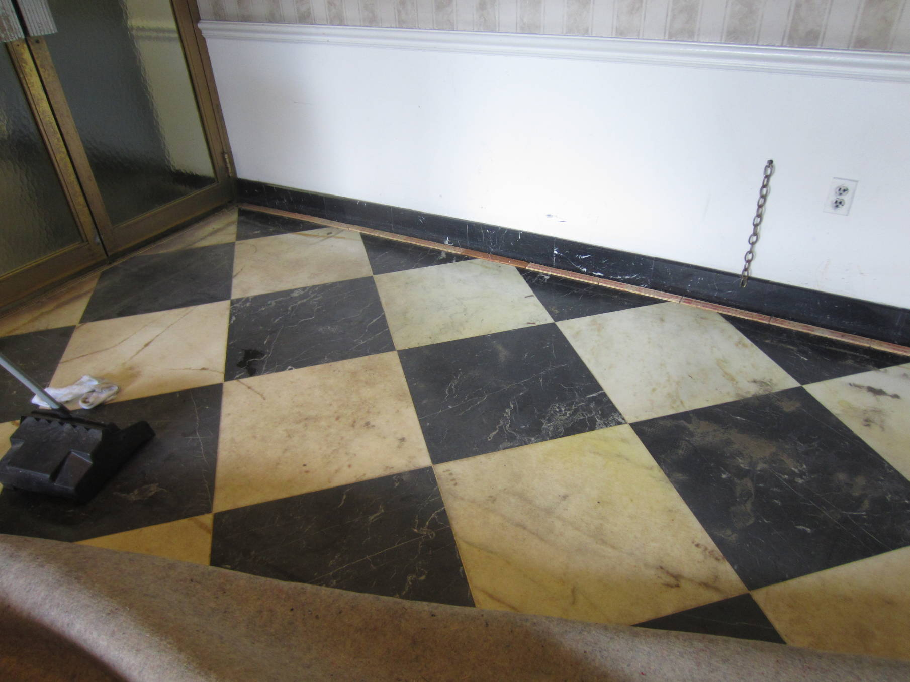 Before  - The hidden treasure-black and white marble flooring was found under the dated carpet.