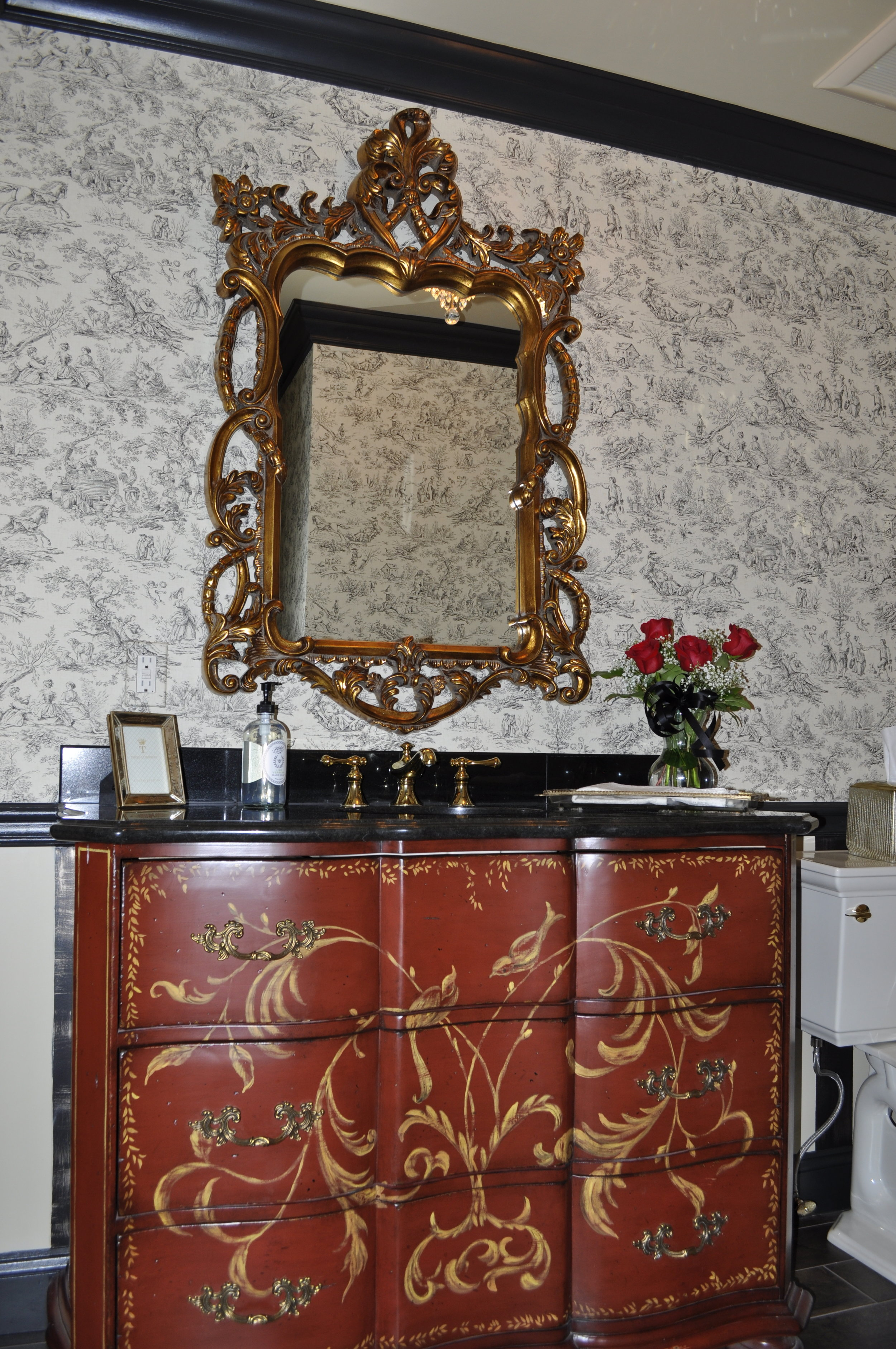 After:  The converted chest and the simple black granite are the perfect pairing. The gold,hand-painted scroll work complements the ornate mirror while beautifully balancing the toile wallpaper. The chic accessories round out the design. No detail is overlooked!