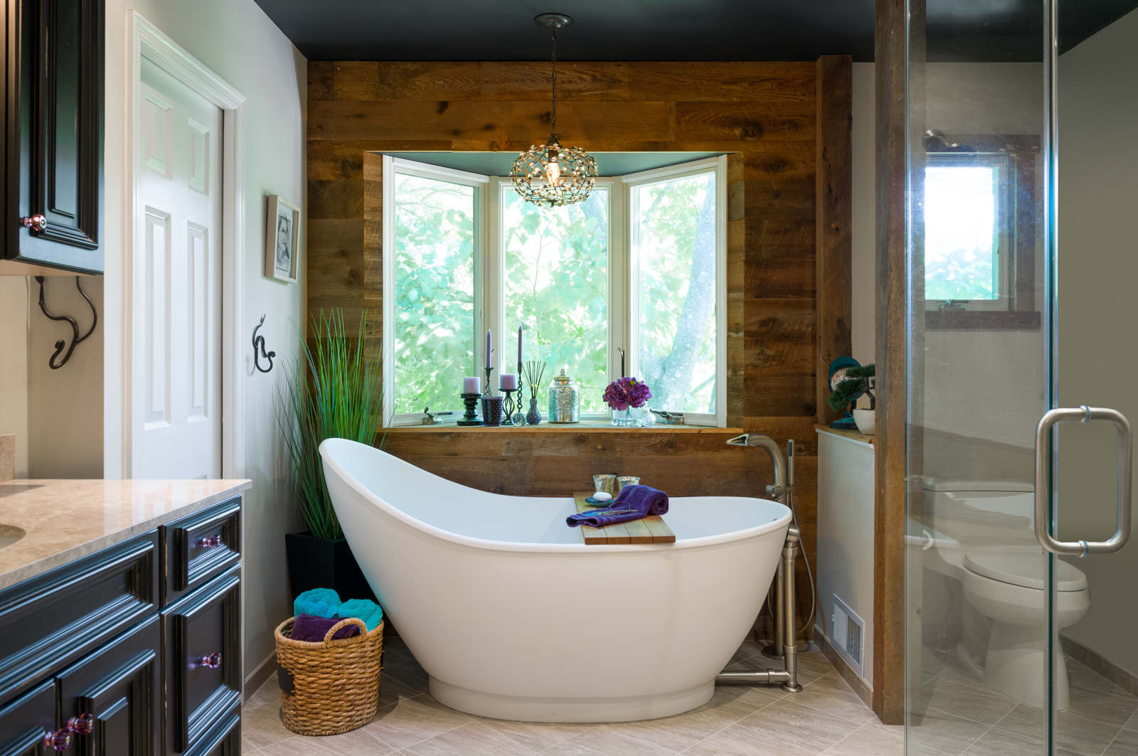 After  - Modern tiles are mixed with reclaimed wood to add texture and the perfect backdrop for the gorgeous tub. We also incorporated a black ceiling,small accents of purple and turquoise (our clients' favorite colors) and a little bling aka the mini chandelier.