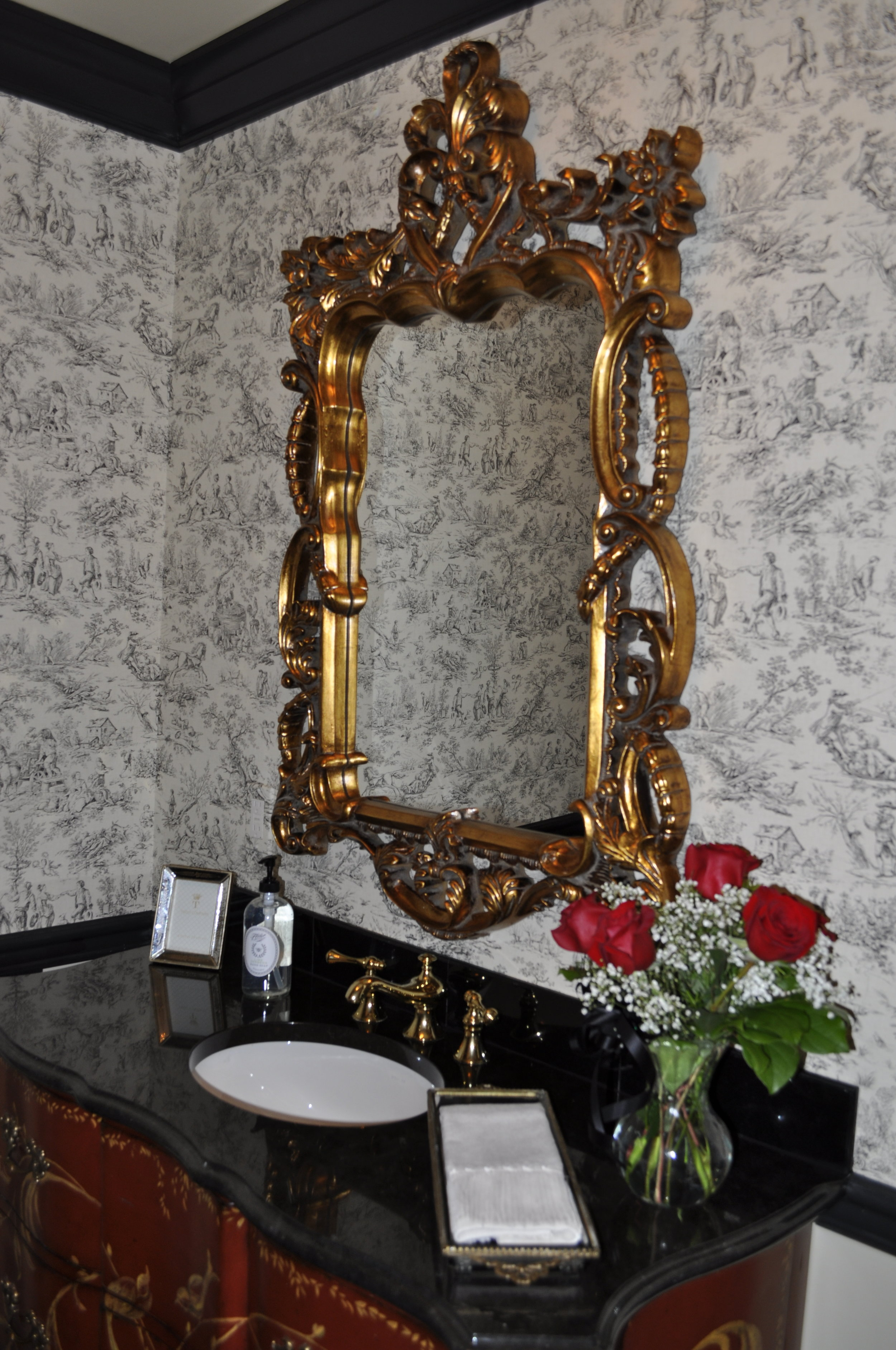 A close up of the beautifully appointed vanity top. The fresh flowers add another pop of red to the room.