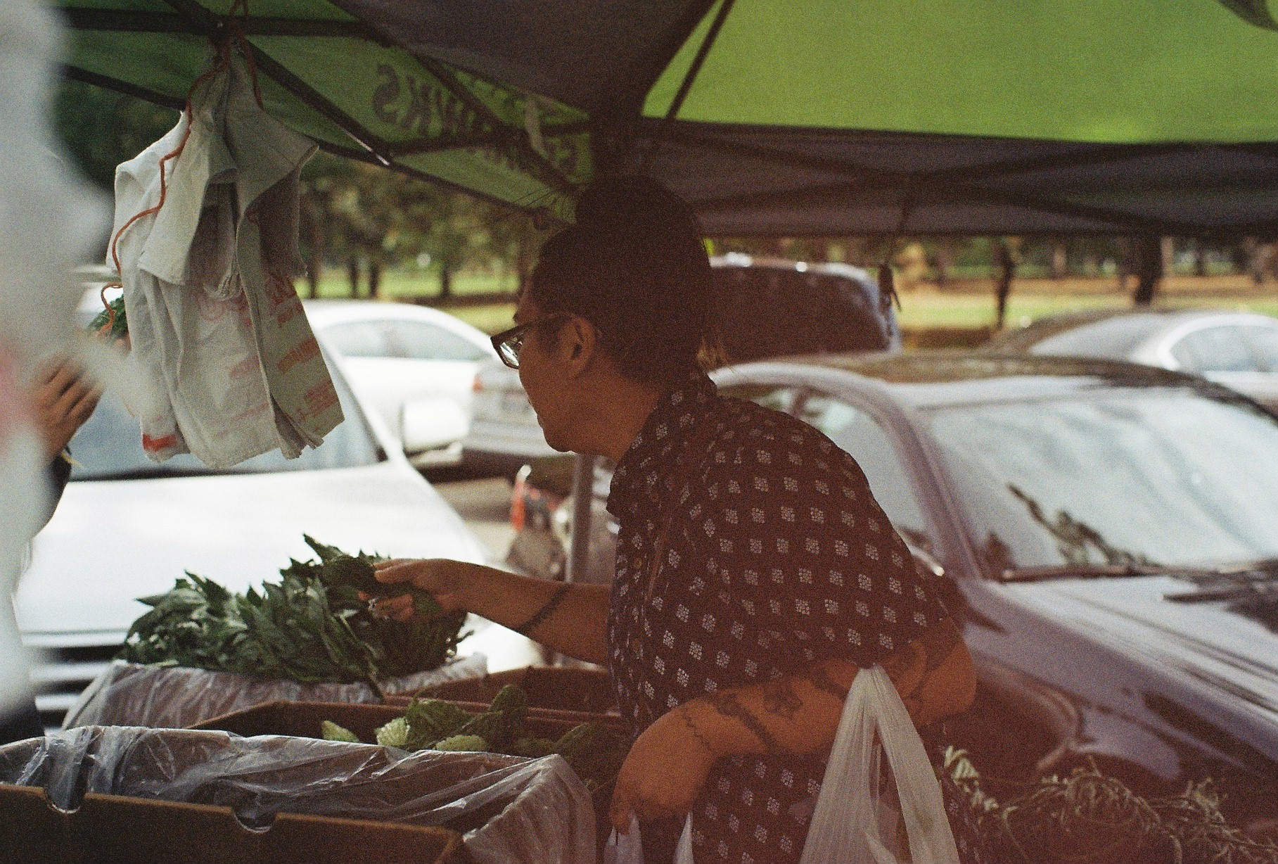 The author visiting Auntie L.'s tent, one of the Ilokano farmers at the Filipino Farmers Market in Seattle, WA. The farmers hail from generations of Filipino-Americans who settled in Wapato, WA who continue to farm there. / Photo by Thanh Hằng Phạm