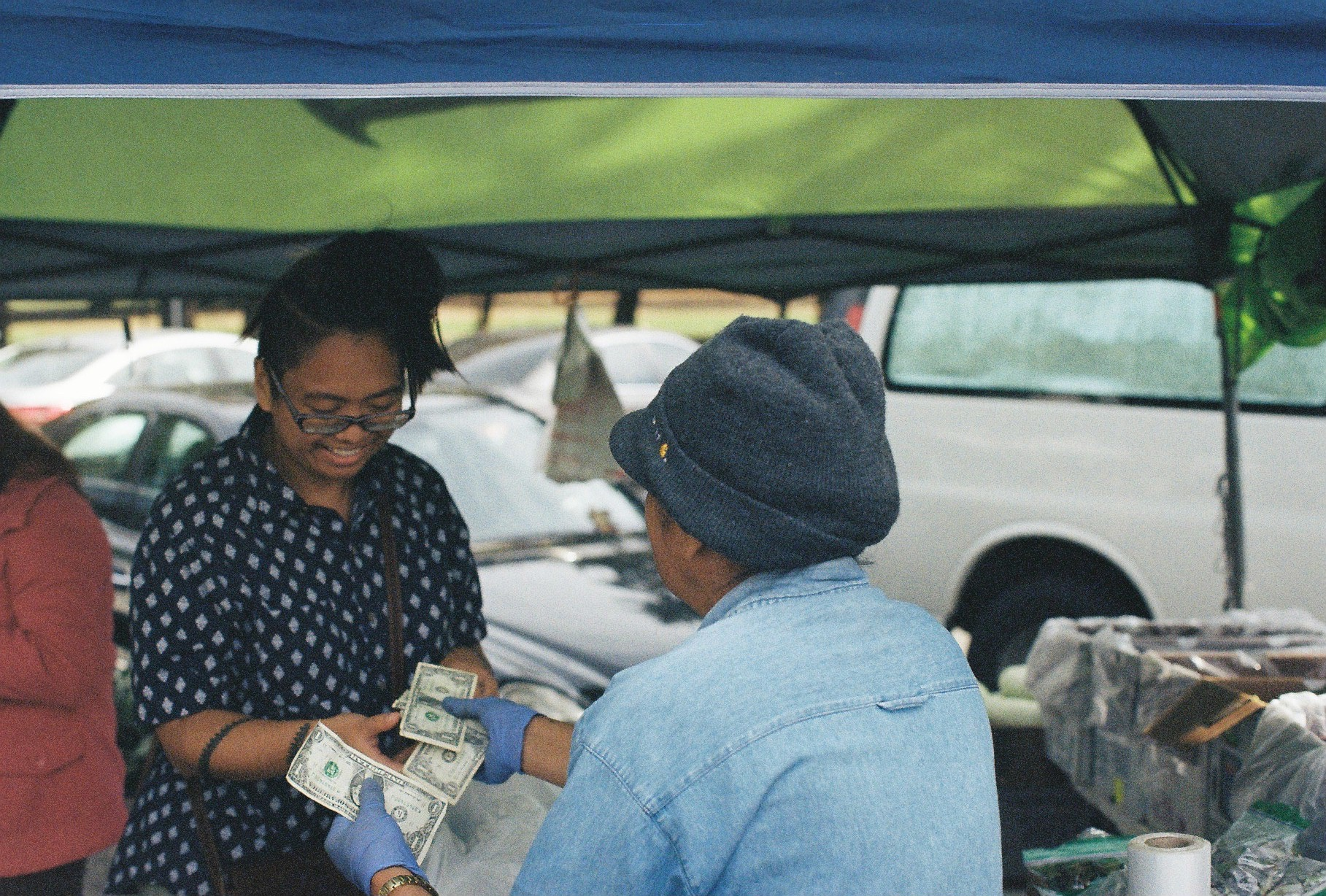 The author smiling during a conversation with Auntie L. while exchanging money for vegetables / Photo by Thanh Hằng Phạm