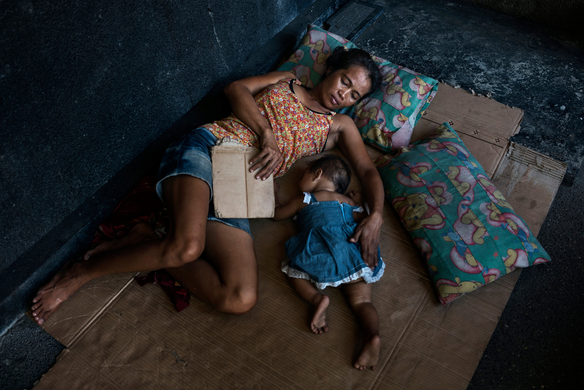 Noemi Canilang, 41, resting in a family mausoleum with her 8-month-old grandchild. She has cared for the mausoleum for 25 years and sleeps there with five members of her family. She receives a monthly stipend of 50 pesos, about $1. (Adam Dean for The New York Times)