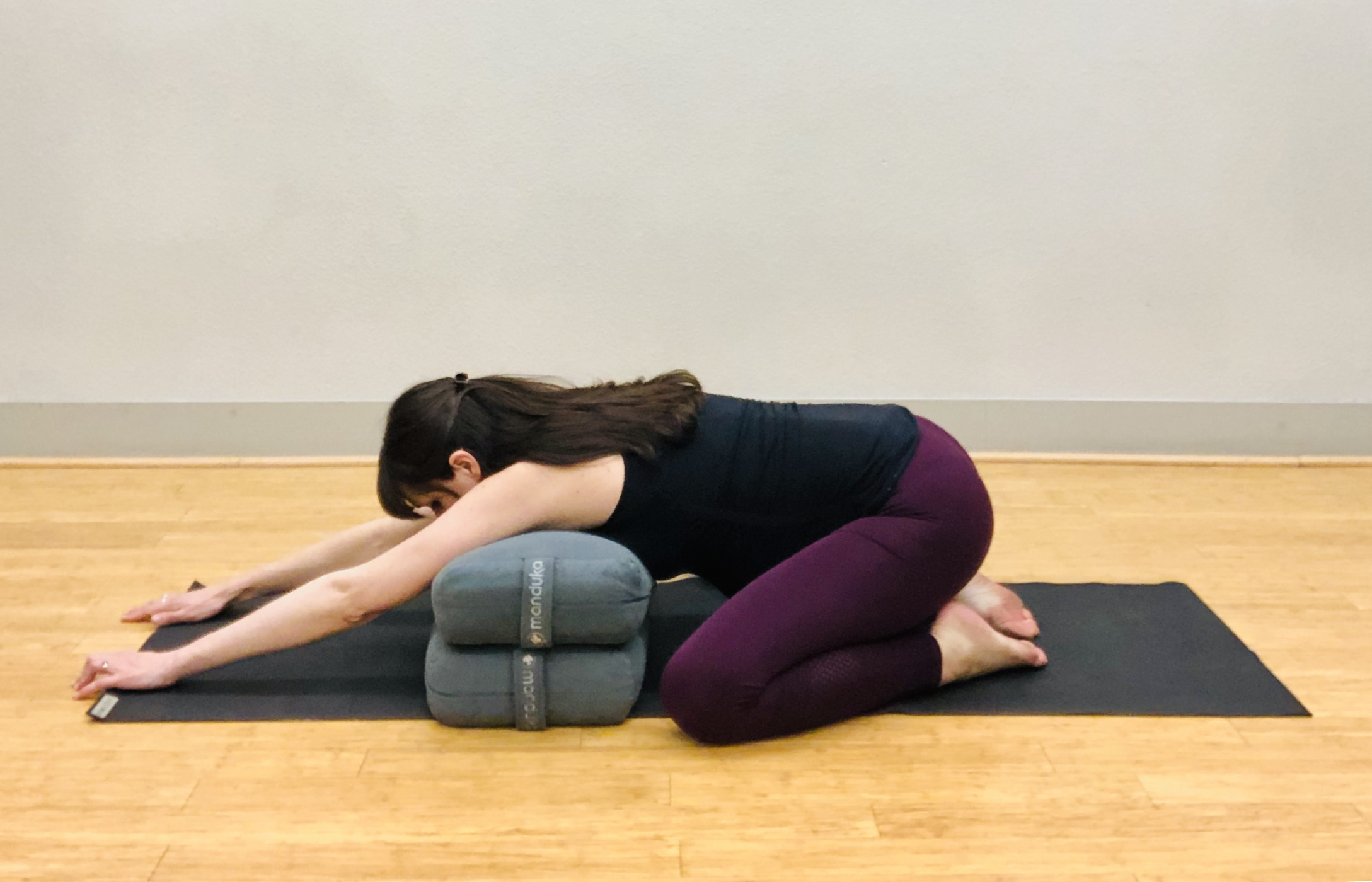 Option #1; Child's Pose with Bolsters or Pillows. Rest chest on cushions and extend arms out. Knees are wide.