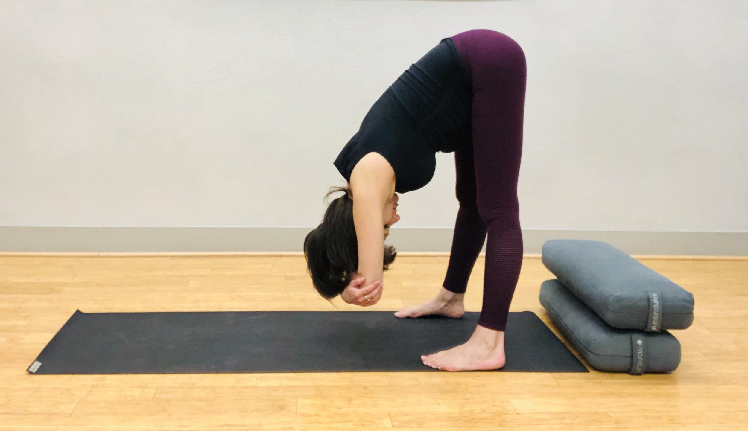Standing Forward Fold. Keep feet wide to accommodate belly. Options include leaving hands on floor or grabbing elbows to hang and stretch neck and spine.