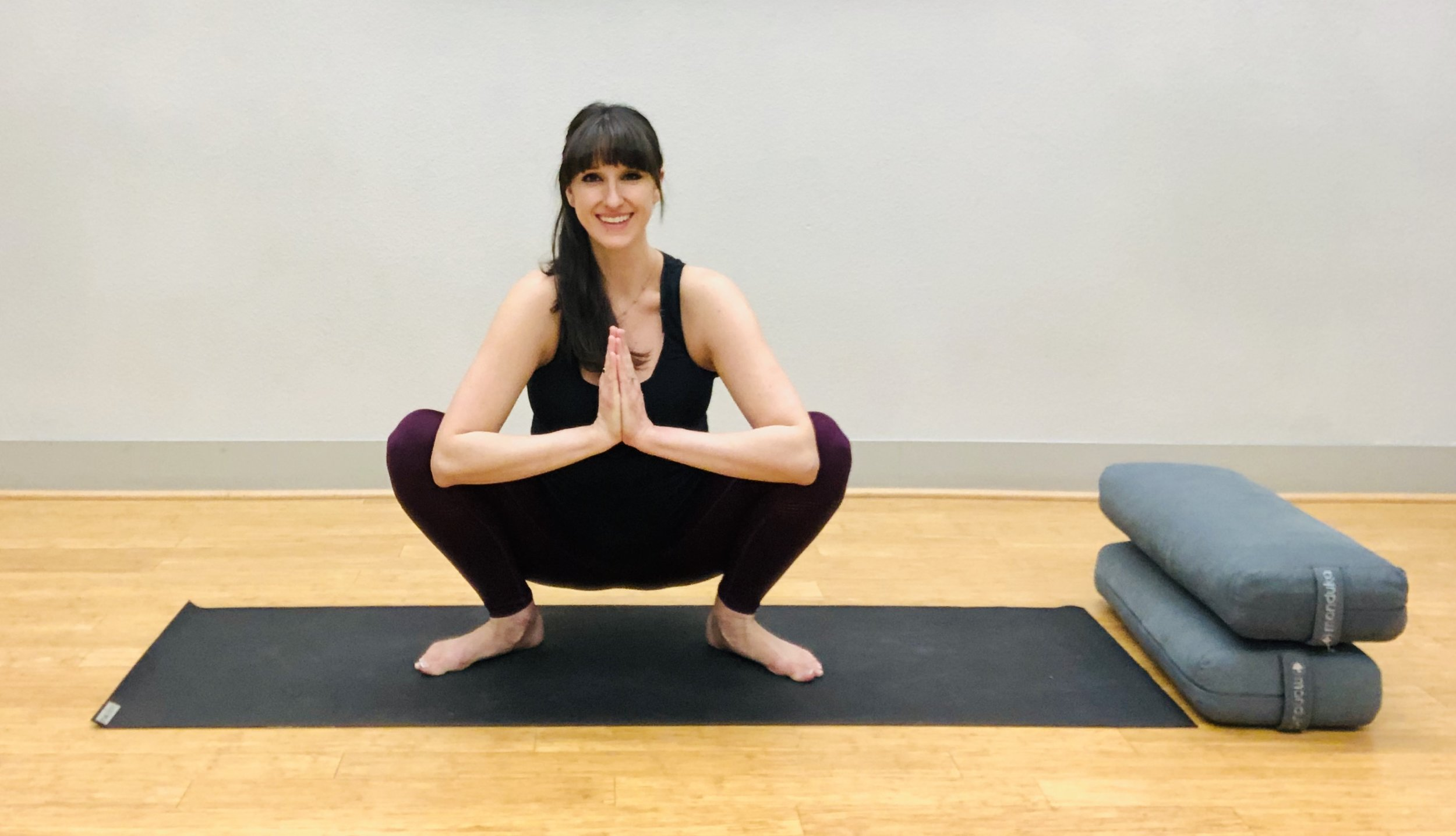 Squat again to come to floor. Other options include sitting on a ball, bolster or pillow. Heels may be lifted, but aim to keep feet wide and flat on the floor. See video for partner-assisted variations!