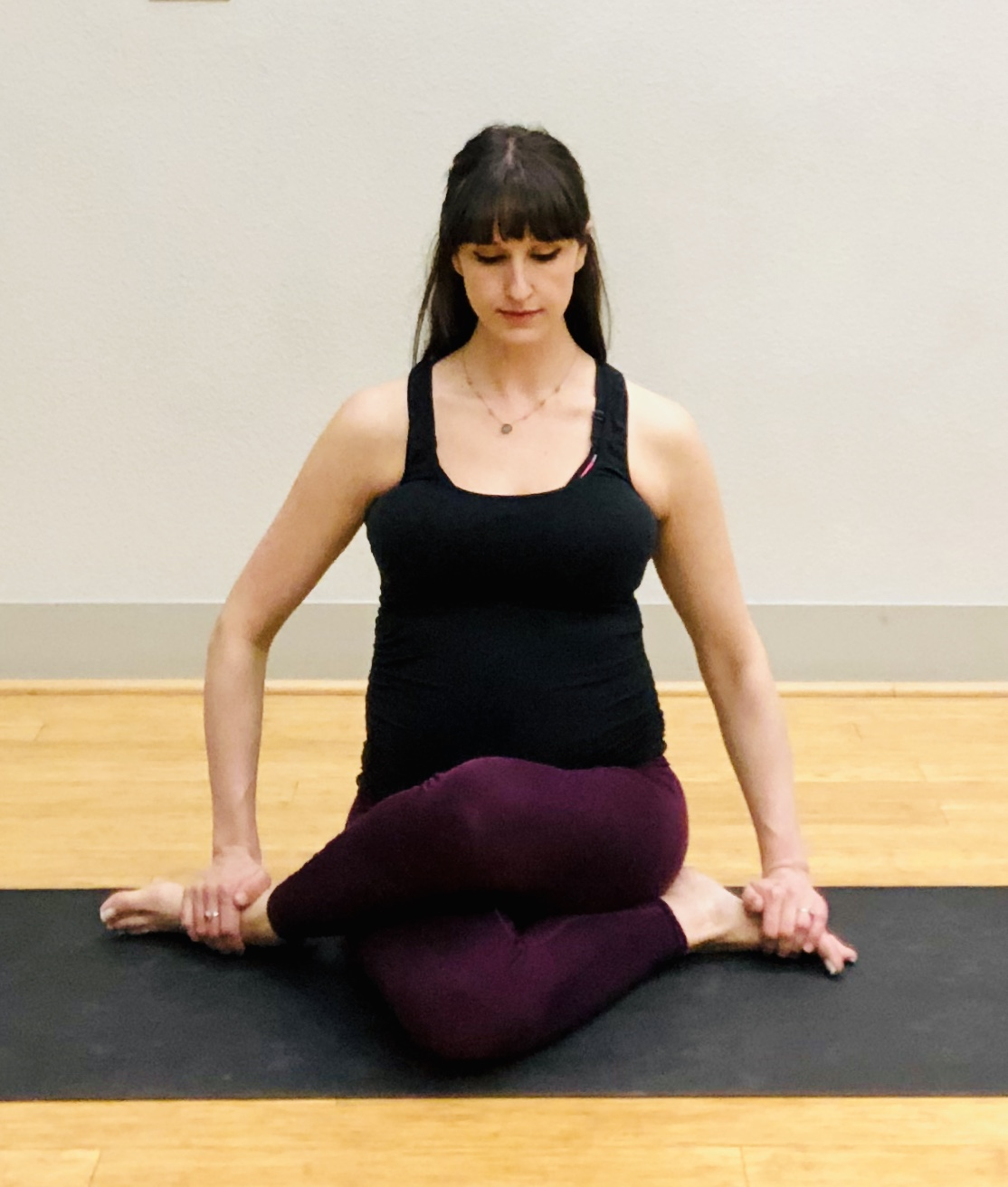 Cow Face Pose. Stack knees one on top of the other. SIt on a block or bolster if either hip is lifted from floor or if knees are unable to cross.